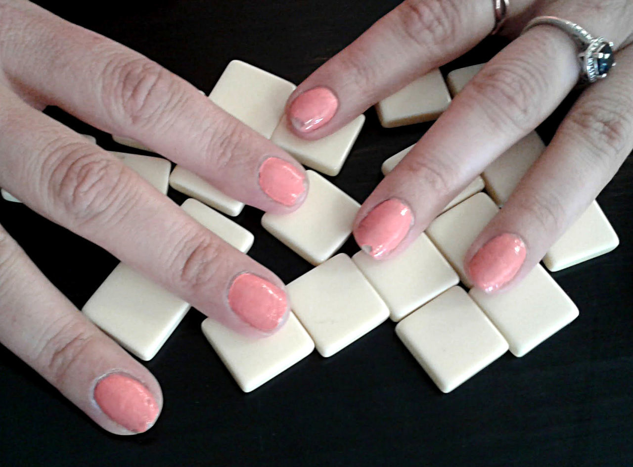 A young woman's hands with peach nail polish, cover up her game tiles. Adult Black Background Chipped Nails Close-up Day Fingers Game Hiding Human Finger Human Hand Indoors  Large Group Of Objects Manicure Nail Polish One Person Playing Games