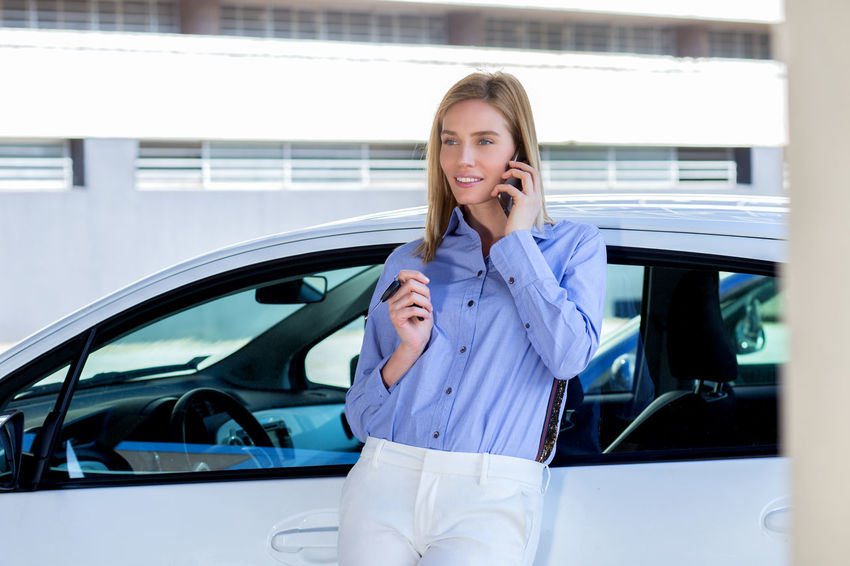 Beautiful young woman with car Answering Car Communication Connection Consumerism Convenience Customer  Day Front View Holding Land Vehicle Mobile Phone Mode Of Transport One Person Portability Portable Information Device Standing Talking Technology Transportation Using Phone Wireless Technology Women Young Adult Young Women