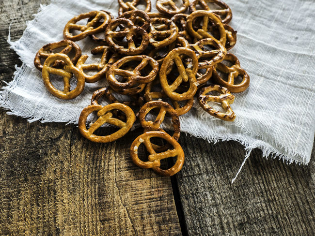 Heap of fresh Wheat salt pretzels on hessian linen fabric cloth and wooden table Cloth Fabric Fresh Heap Hessian Linen Pretzels Salt Table Wheat Wooden