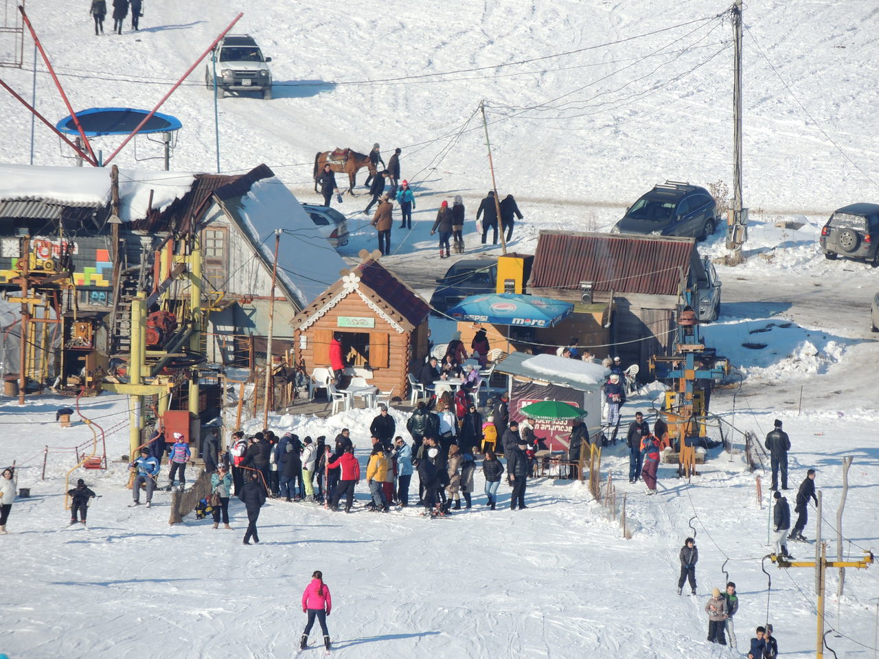 large group of people, winter, snow, cold temperature, leisure activity, real people, day, winter sport, lifestyles, mixed age range, outdoors, frozen, men, women, enjoyment, built structure, vacations, nature, ice-skating, architecture, ski holiday, ice rink, building exterior, ski lift, crowd, warm clothing, sky, people, adult, adults only