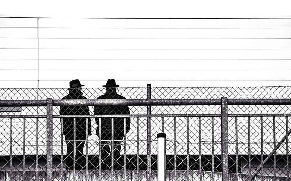 SIMPLY People Watching Wearing Hat Behind The Barriers Monochrome Photography Blackandwhite Conversation Scenery Shots Multiple Layers Fences Streeetphotography Beauty In Ordinary Things