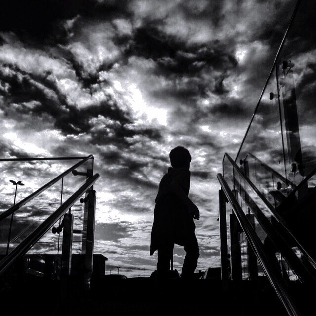 sky, cloud - sky, silhouette, childhood, full length, real people, one person, outdoors, boys, standing, low angle view, built structure, lifestyles, day, nature, architecture, people