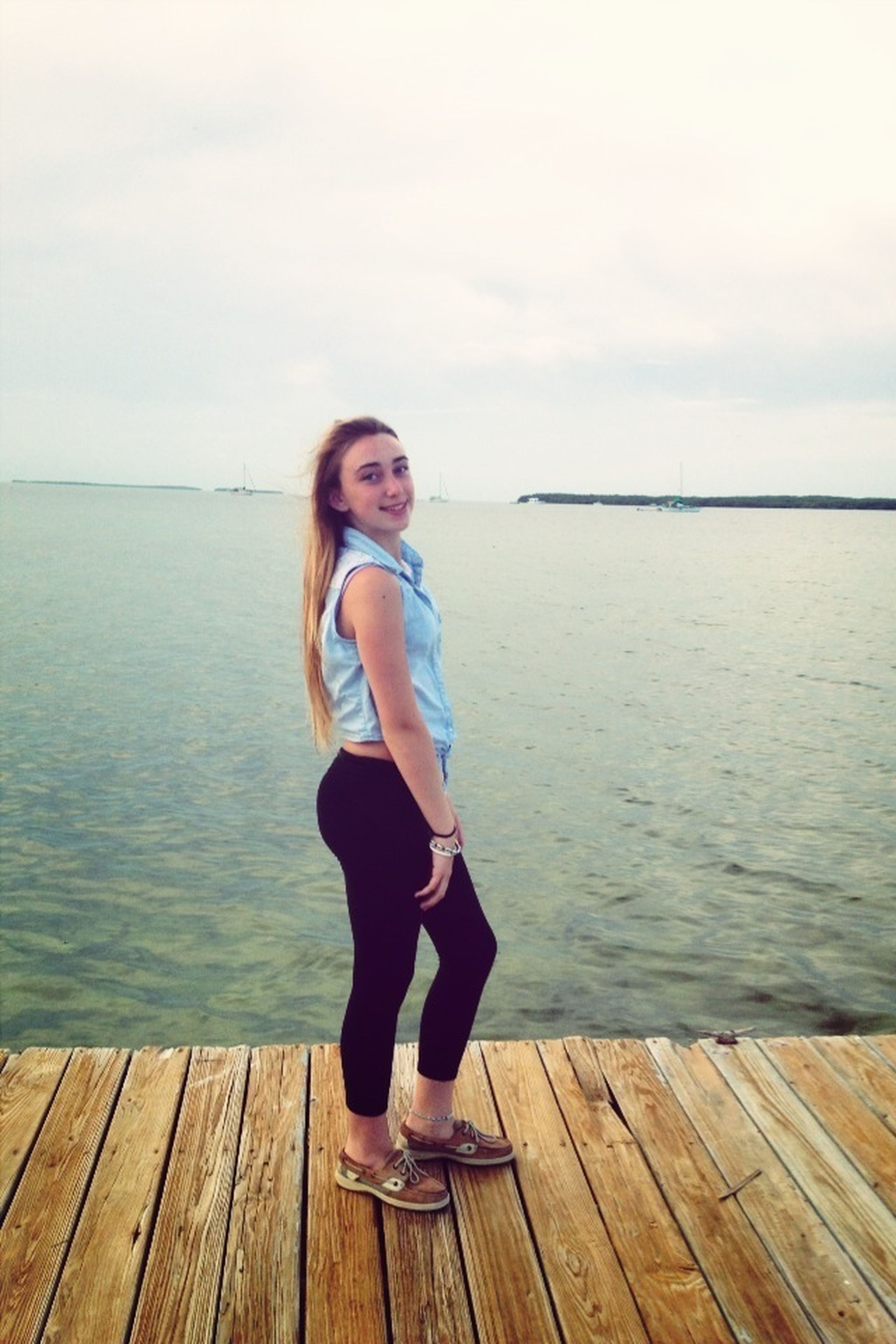 water, full length, lifestyles, casual clothing, wood - material, person, young adult, leisure activity, pier, standing, sea, looking at camera, young women, portrait, tranquility, sky, wooden, sitting