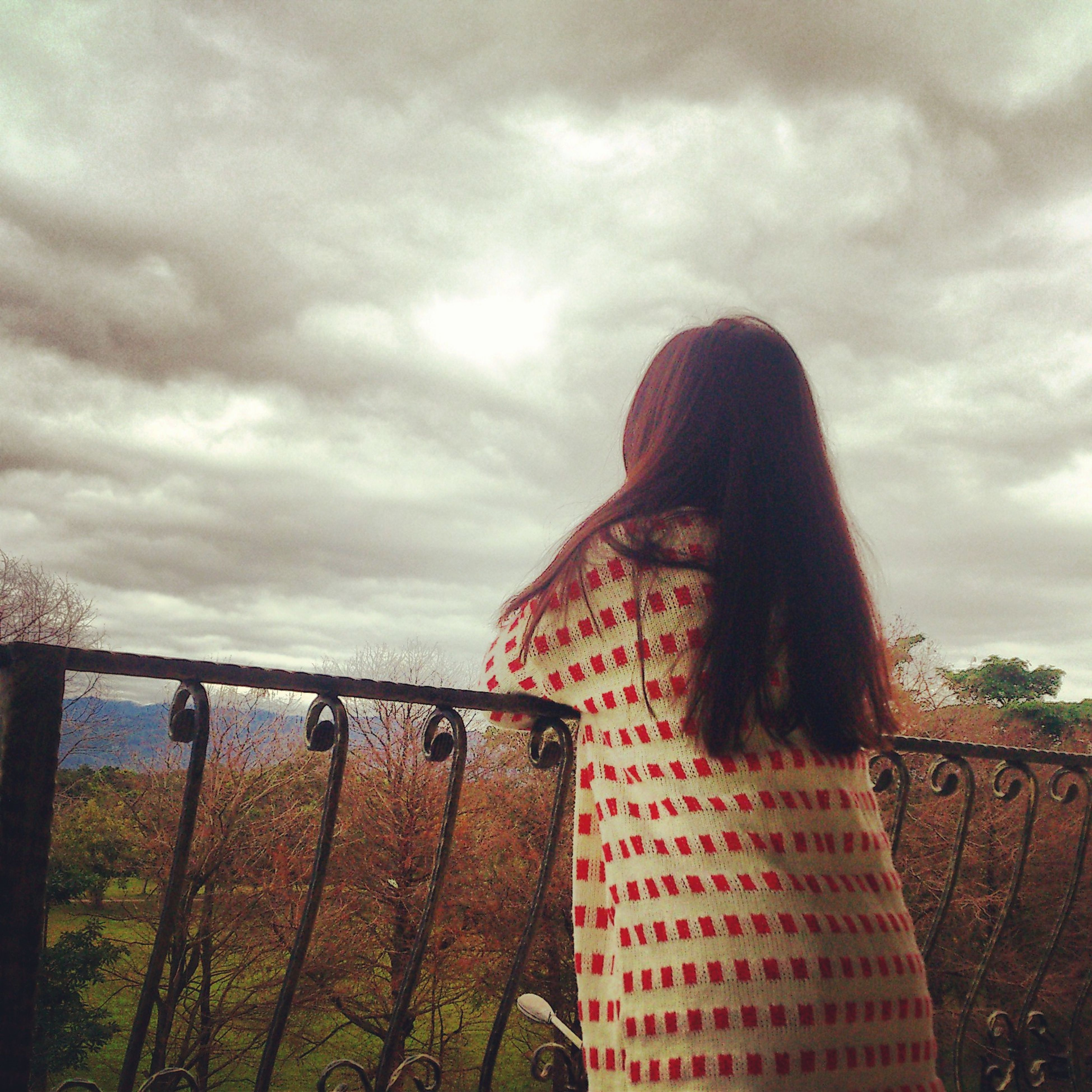 sky, cloud - sky, cloudy, cloud, leisure activity, lifestyles, rear view, nature, tranquility, overcast, railing, standing, weather, casual clothing, tranquil scene, person, scenics, day