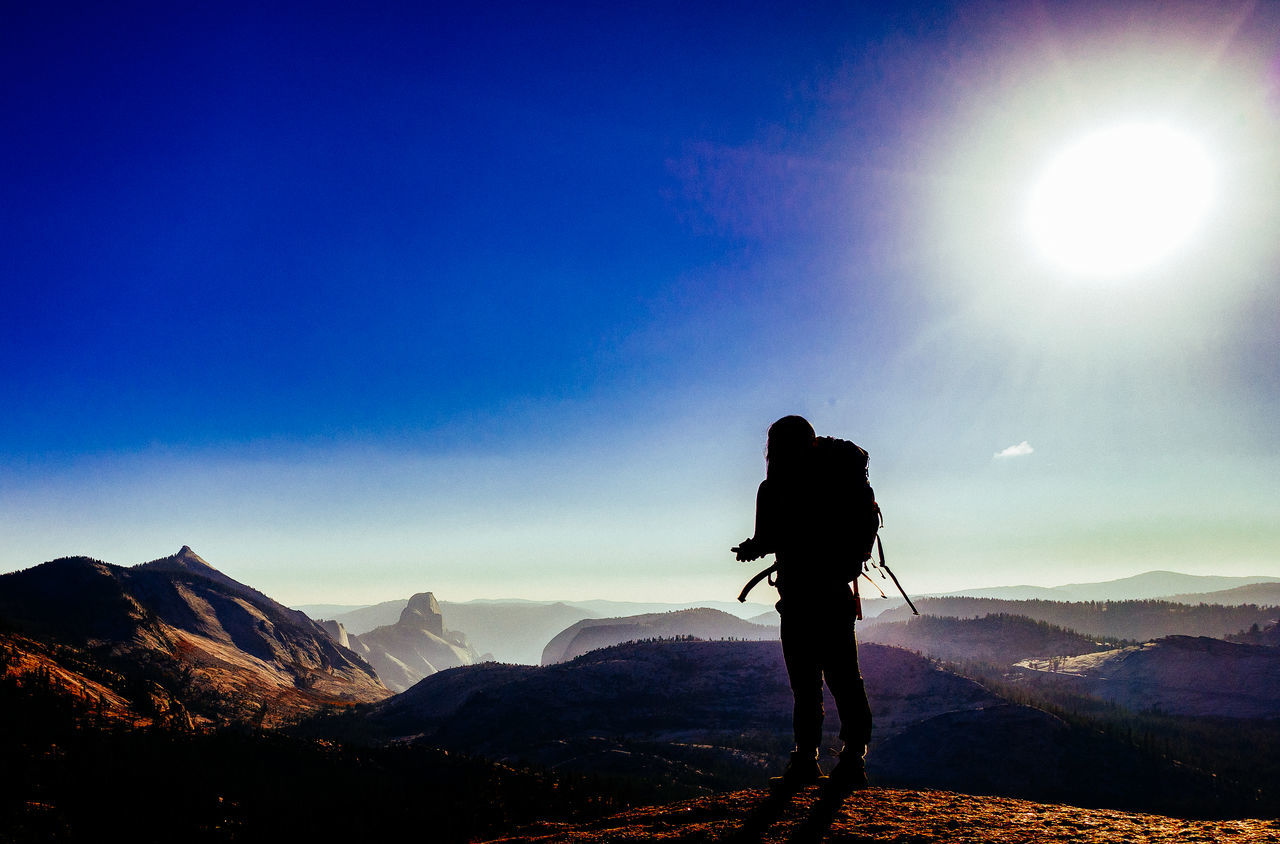 mountain, hiking, adventure, nature, real people, full length, mountain range, backpack, beauty in nature, standing, silhouette, leisure activity, outdoors, sky, scenics, one person, sunlight, tranquility, sun, rear view, landscape, tranquil scene, lifestyles, day, clear sky, men, cold temperature, extreme sports, people