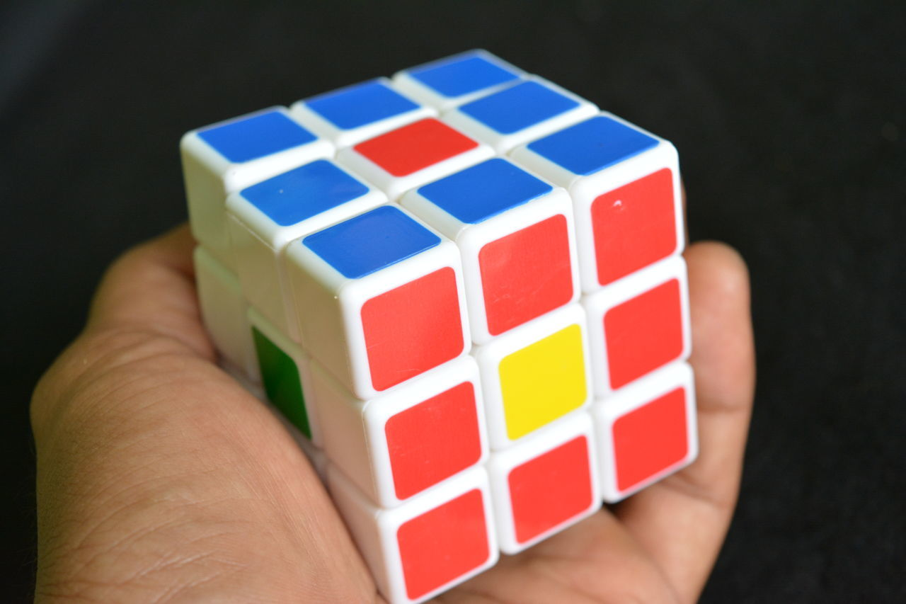 Black Background Close-up Day Holding Human Body Part Human Finger Human Hand Indoors  Leisure Activity Leisure Games Lifestyles Multi Colored One Person People Puzzle  Real People Red Rubik Rubik's Cube Strategy Toy Block Unrecognizable Person