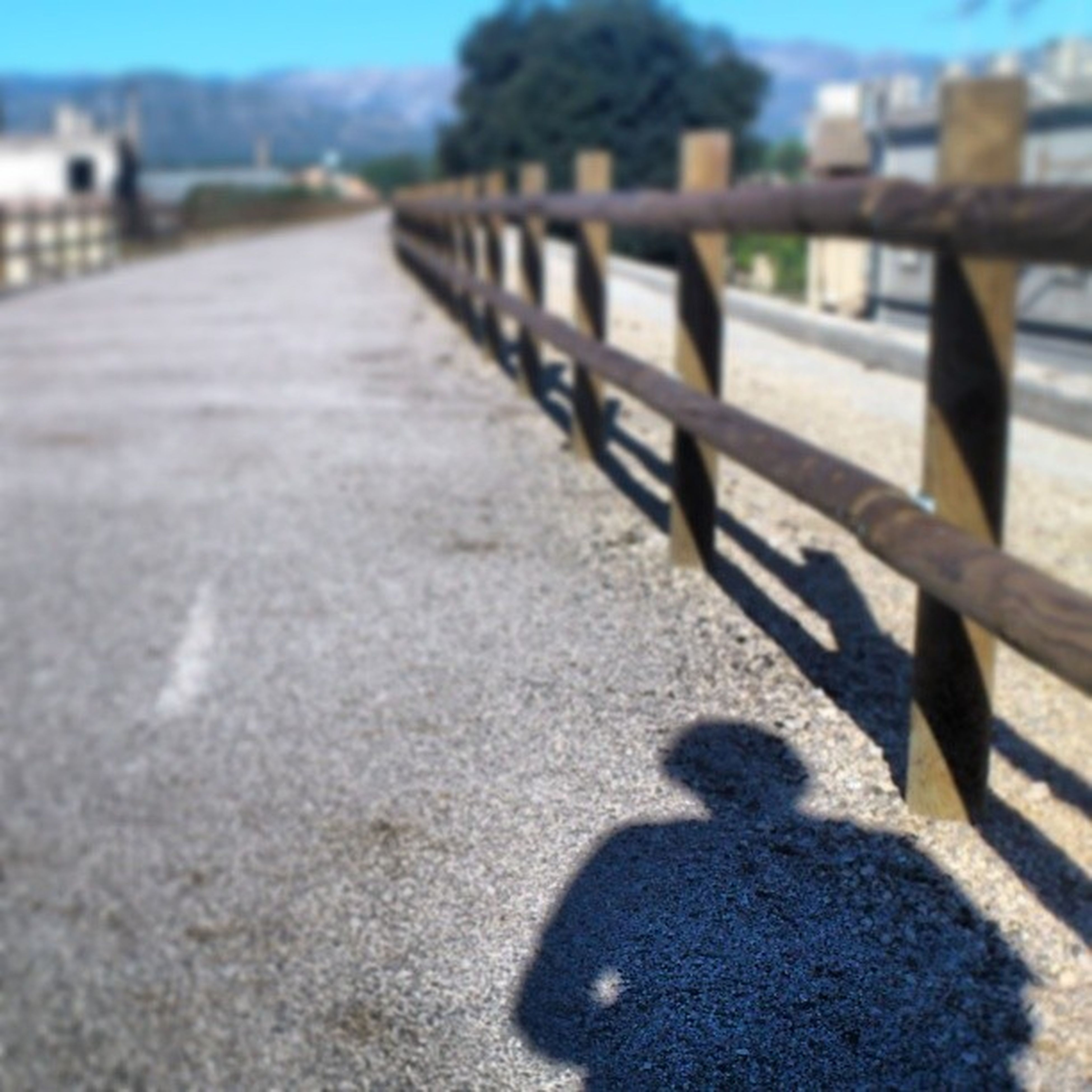 shadow, focus on foreground, selective focus, sunlight, surface level, street, incidental people, outdoors, railing, day, road, close-up, built structure, bench, sunny, walking, sidewalk, nature, sand