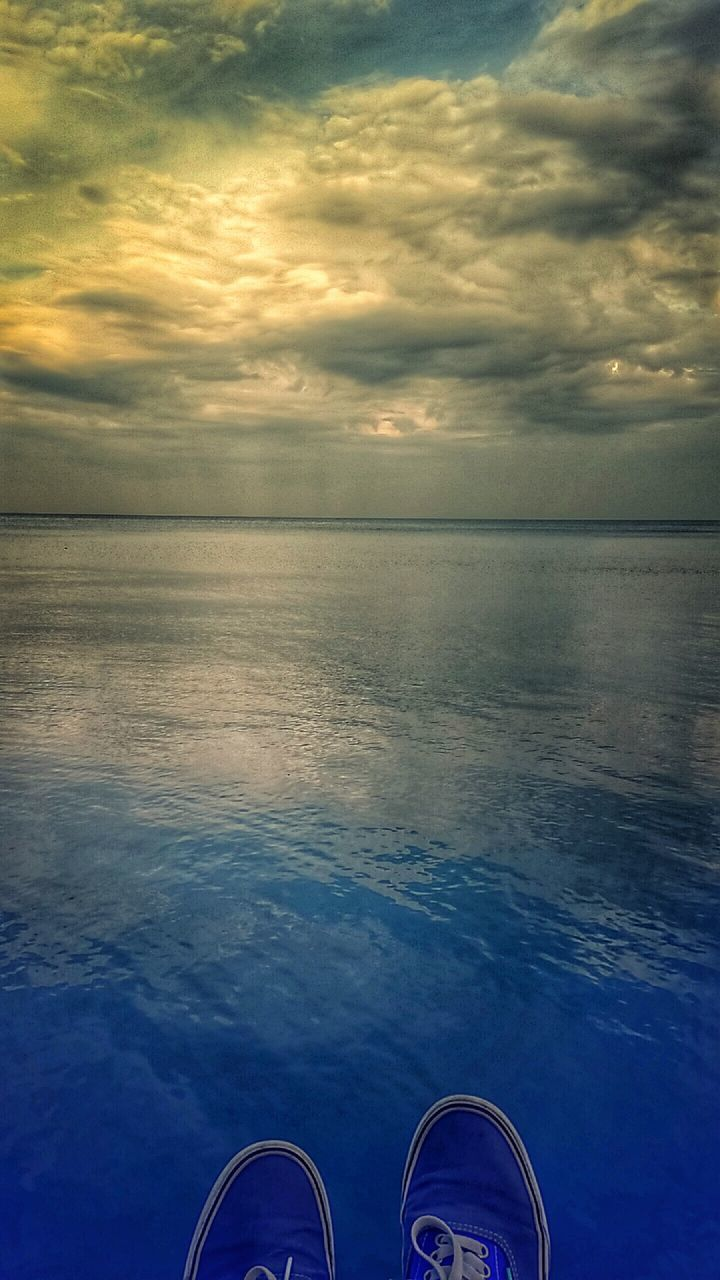 water, sky, horizon over water, sea, cloud - sky, shoe, low section, human leg, nature, pair, outdoors, scenics, tranquility, tranquil scene, beauty in nature, sunset, blue, one person, day, human body part