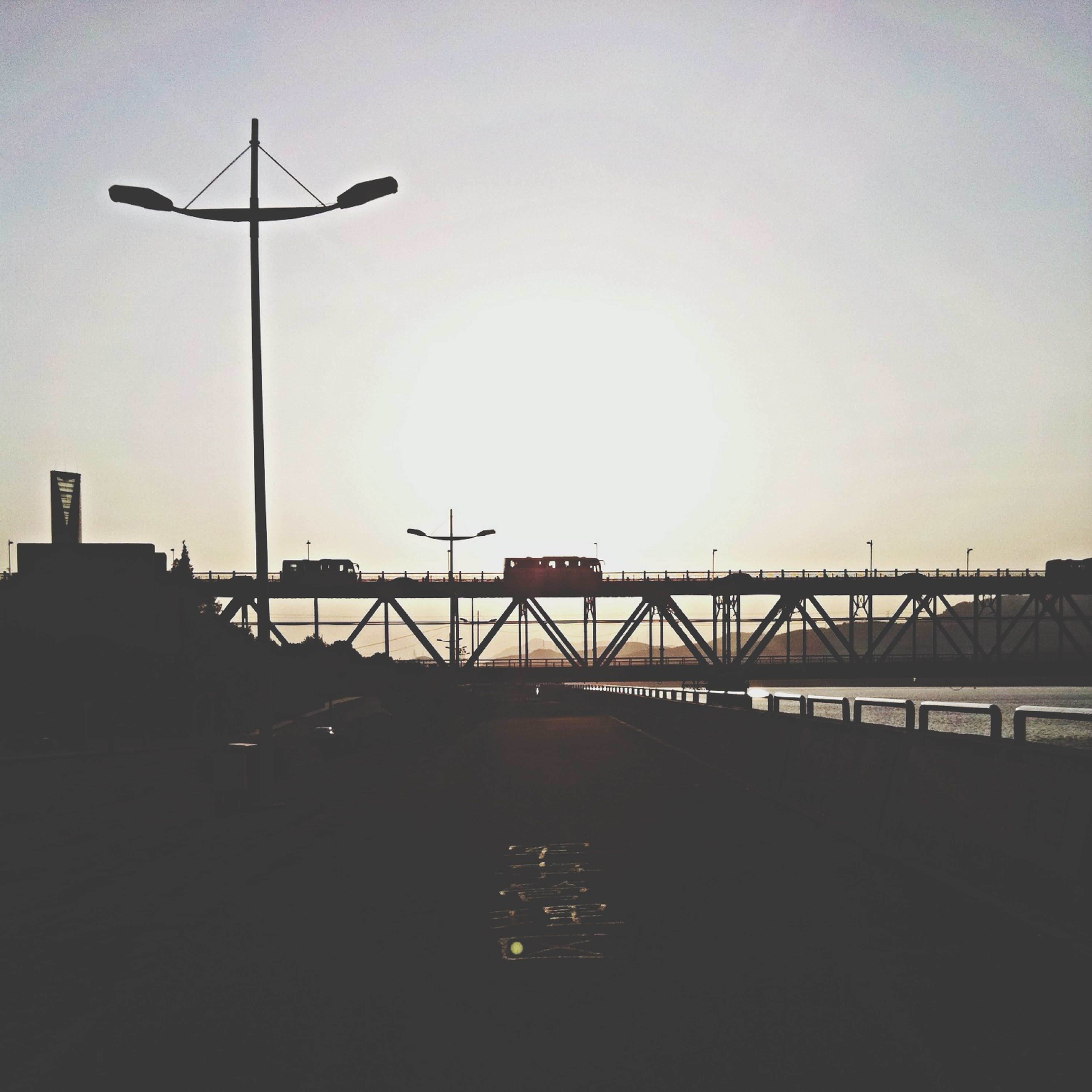 clear sky, copy space, street light, silhouette, built structure, architecture, transportation, sunset, sky, low angle view, lighting equipment, building exterior, connection, dusk, railing, outdoors, no people, nature, road, bridge - man made structure