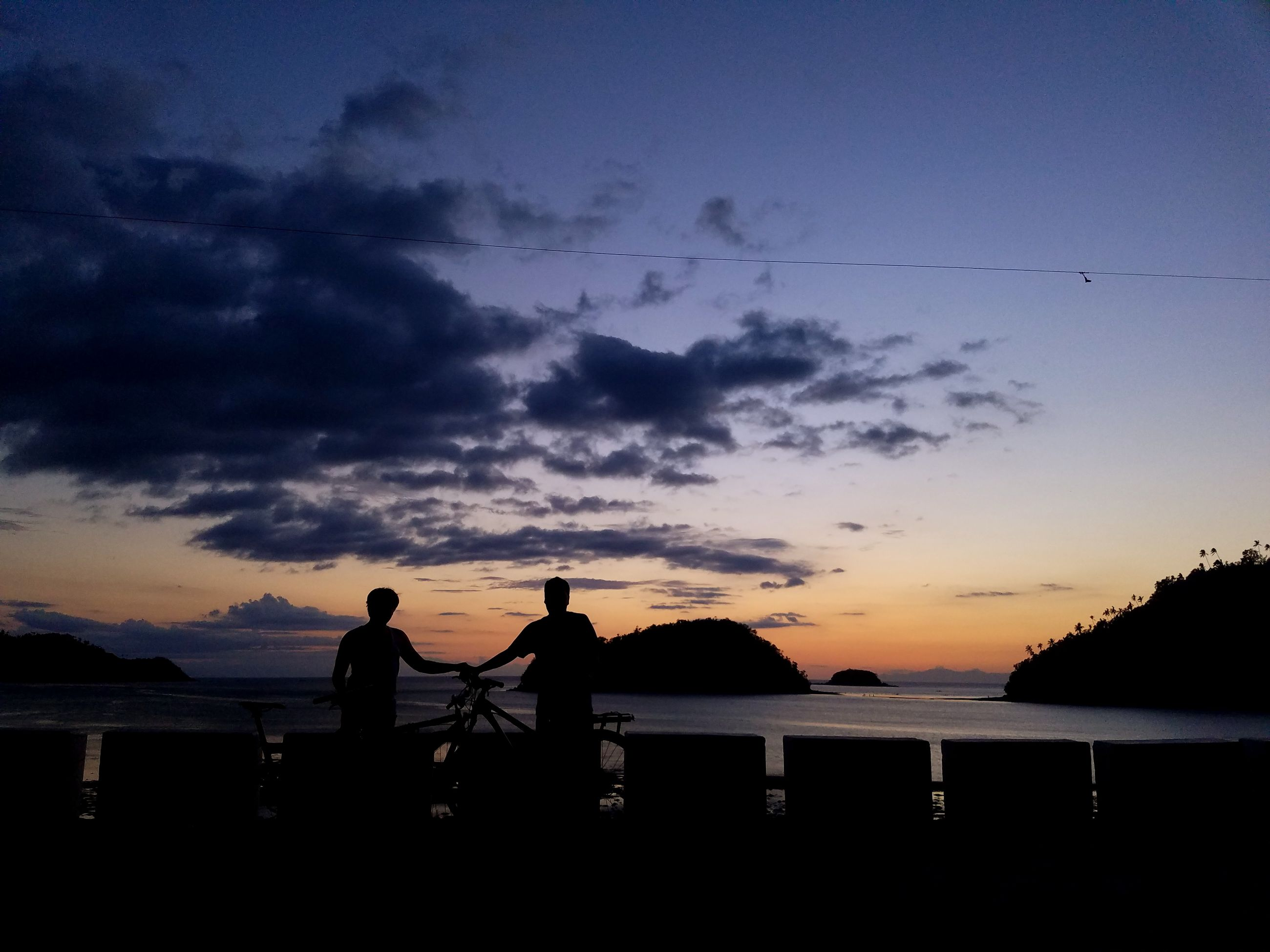 sunset, silhouette, sky, nature, water, beauty in nature, outdoors, cloud - sky, scenics, sea, tranquil scene, fishing, dusk, tranquility, real people, two people, men, nautical vessel, standing, tree, day, people