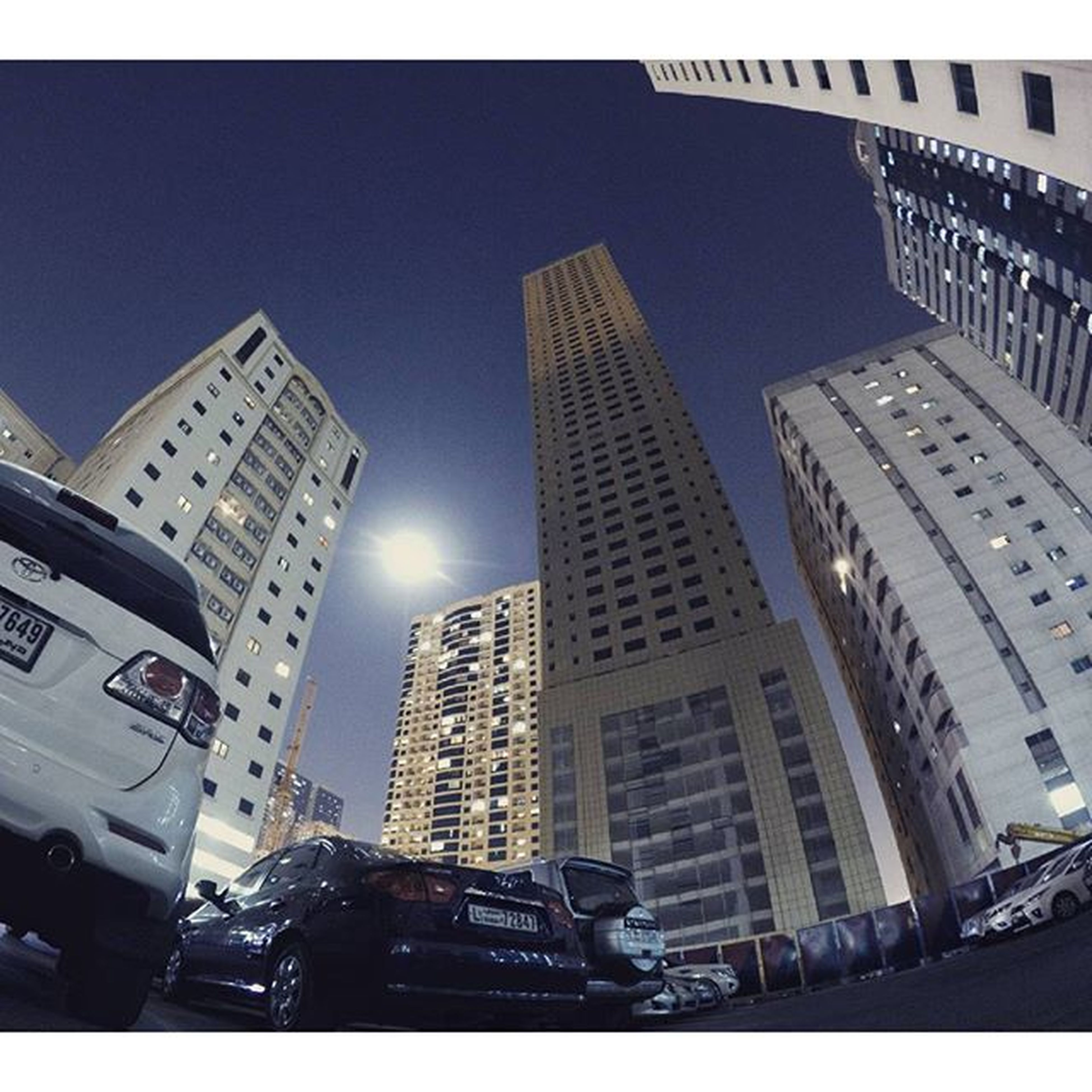 building exterior, architecture, city, built structure, skyscraper, car, transfer print, office building, building, city life, tall - high, street, transportation, land vehicle, auto post production filter, city street, modern, tower, low angle view, mode of transport