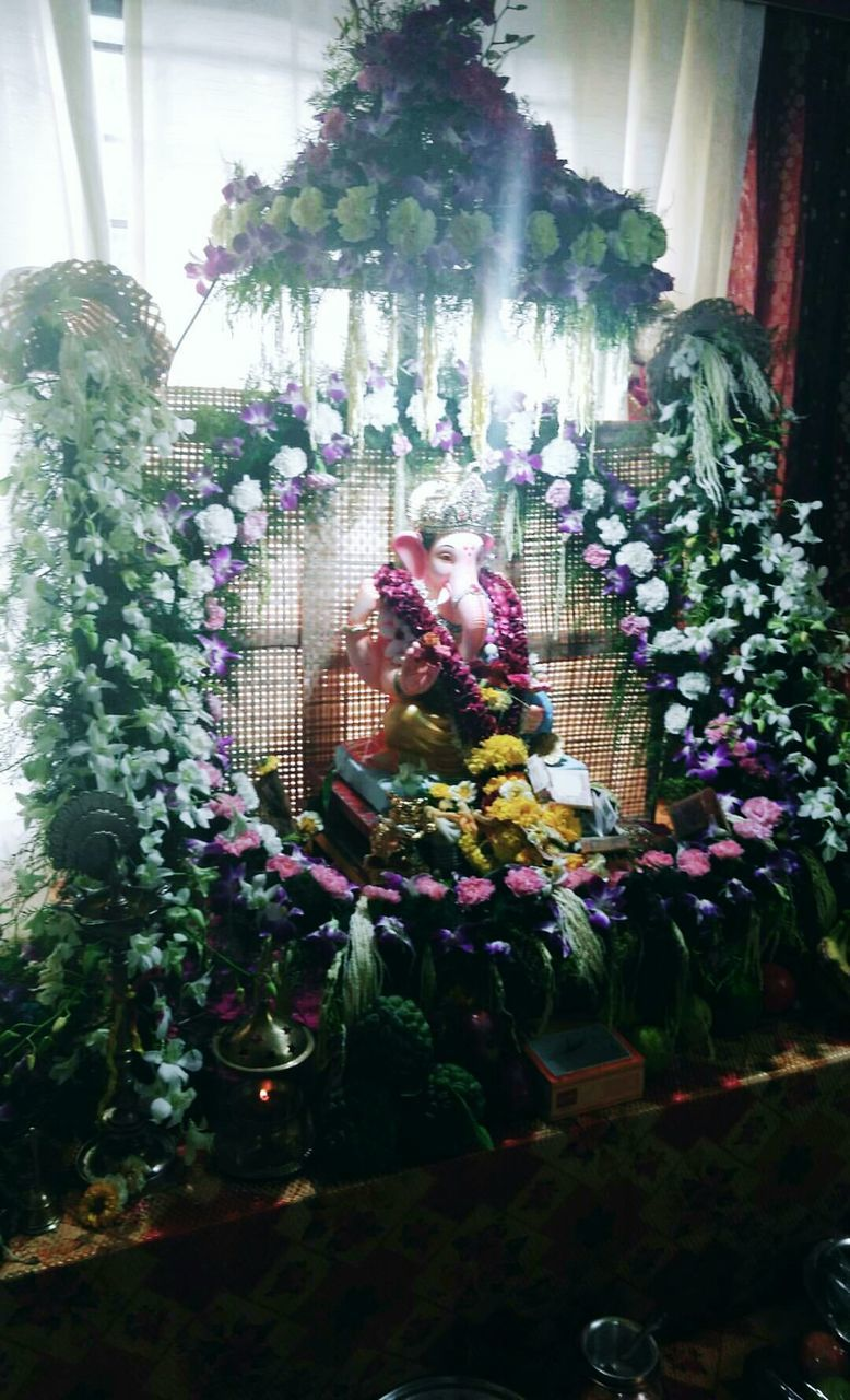 indoors, flower, celebration, statue, religion, plant, spirituality, day, home interior, real people, bouquet, christmas decoration, sculpture, full length, altar, young adult