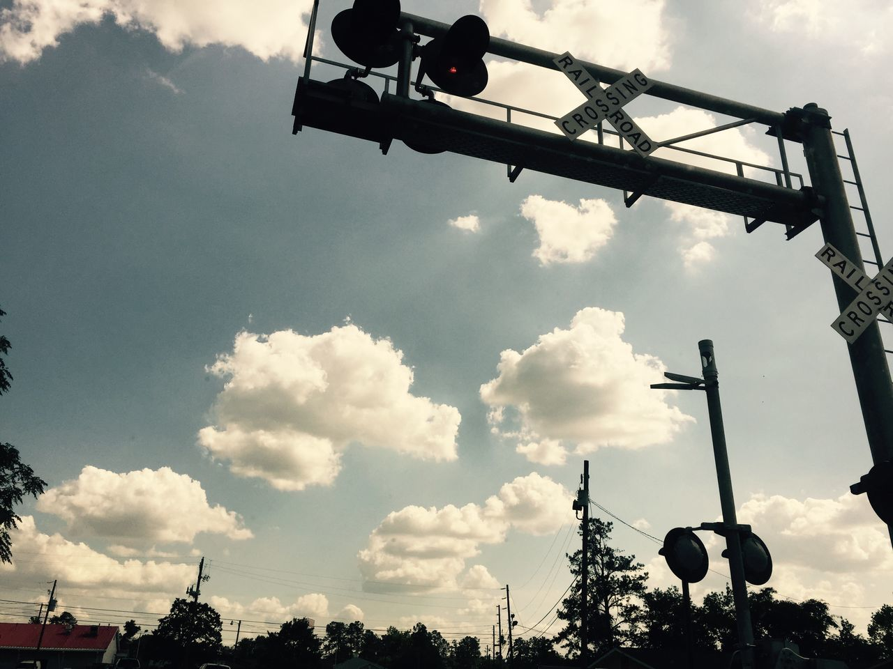 Low Angle View Of Railroad Crossing Sign Against Cloudy Sky