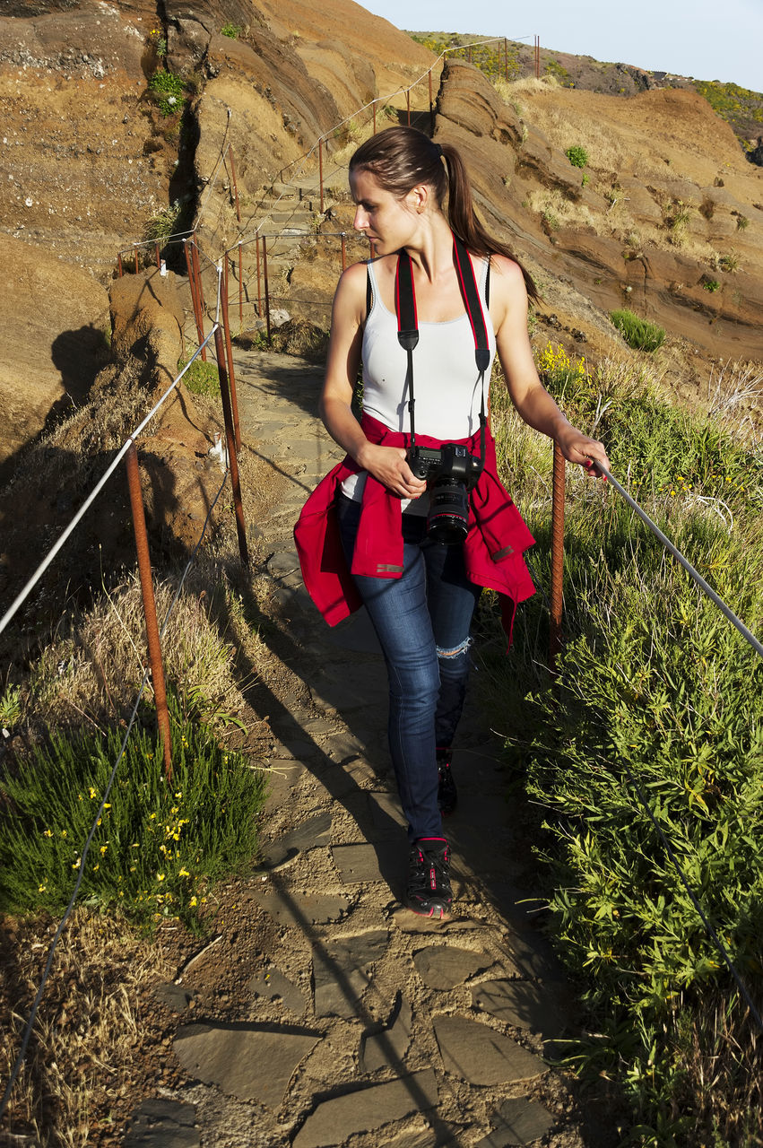 full length, real people, young adult, casual clothing, one person, leisure activity, young women, front view, adventure, lifestyles, day, outdoors, tree, nature, people