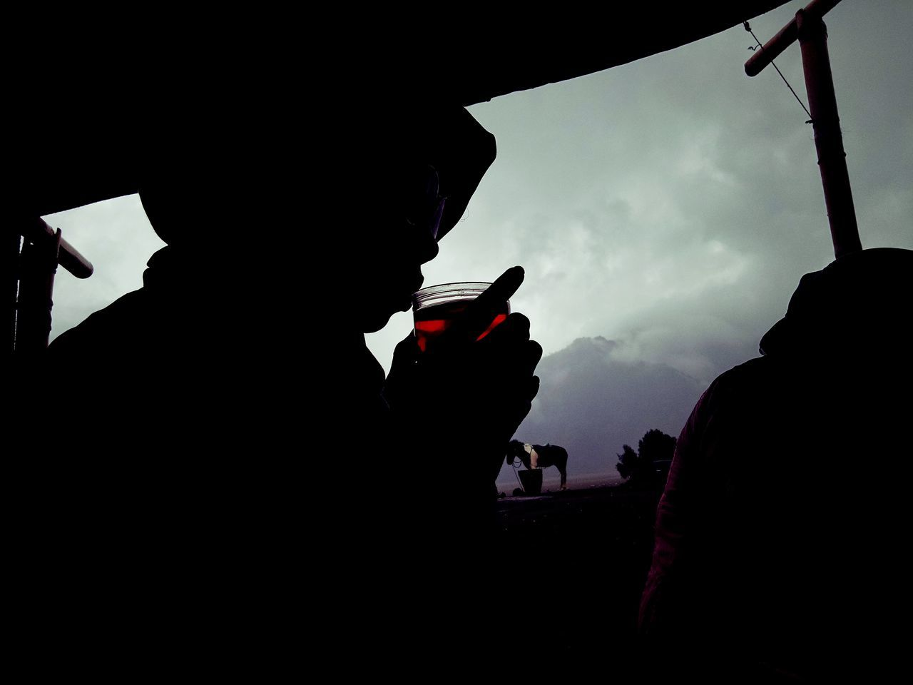 Silhouette Person Having Tea Under Shed Against Sky At Dusk