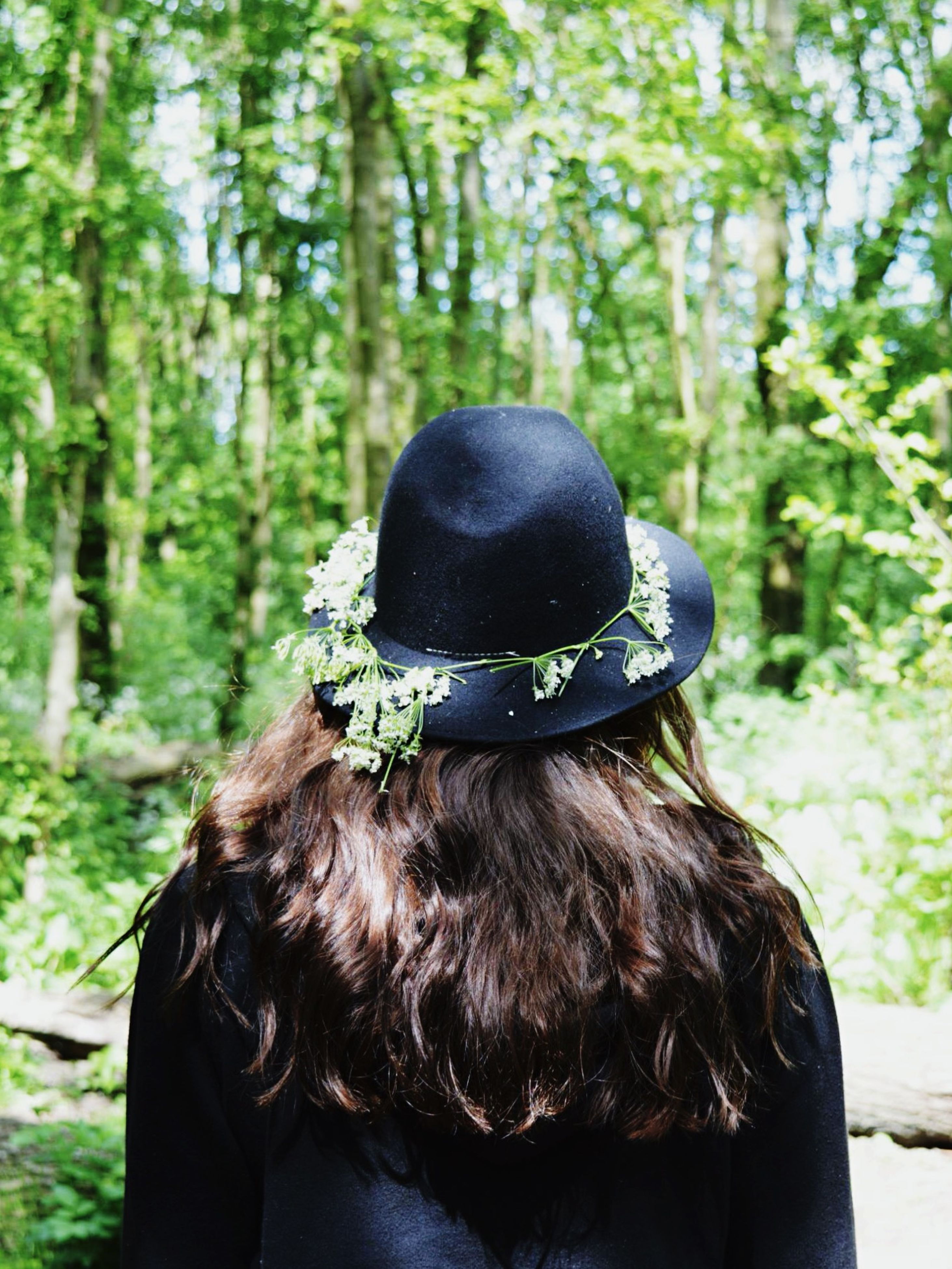 tree, focus on foreground, rear view, headshot, forest, lifestyles, front view, leisure activity, close-up, day, one animal, outdoors, black color, portrait, waist up, casual clothing, hat, young adult