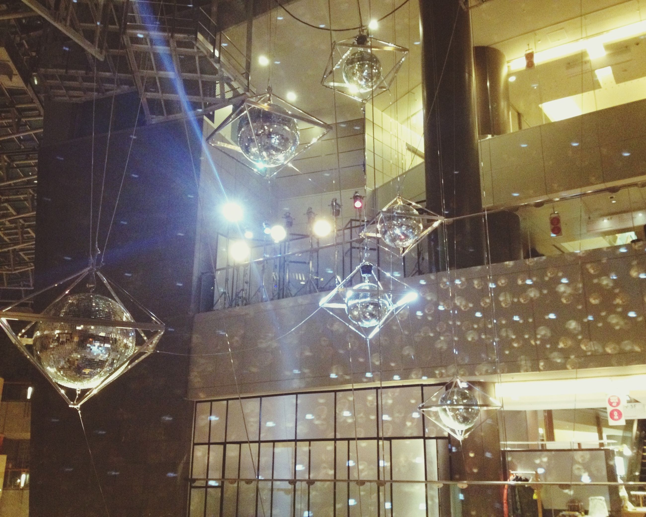 indoors, illuminated, glass - material, window, lighting equipment, transparent, night, built structure, architecture, reflection, electricity, electric light, no people, glass, building exterior, light - natural phenomenon, low angle view, light bulb, hanging, building