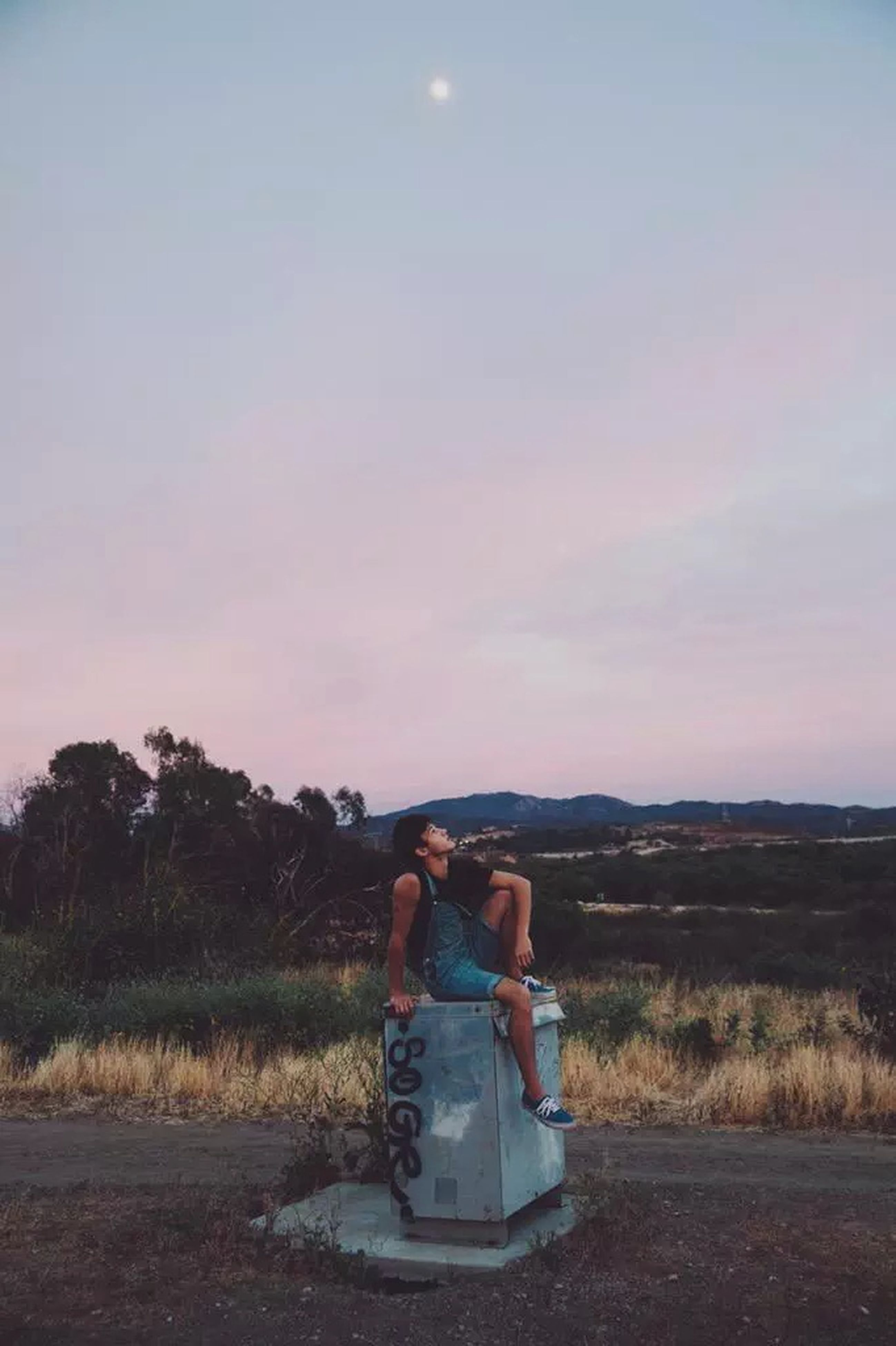 lifestyles, leisure activity, sky, landscape, full length, field, tranquil scene, casual clothing, tranquility, rear view, scenics, nature, sitting, beauty in nature, grass, relaxation, non-urban scene, sunset