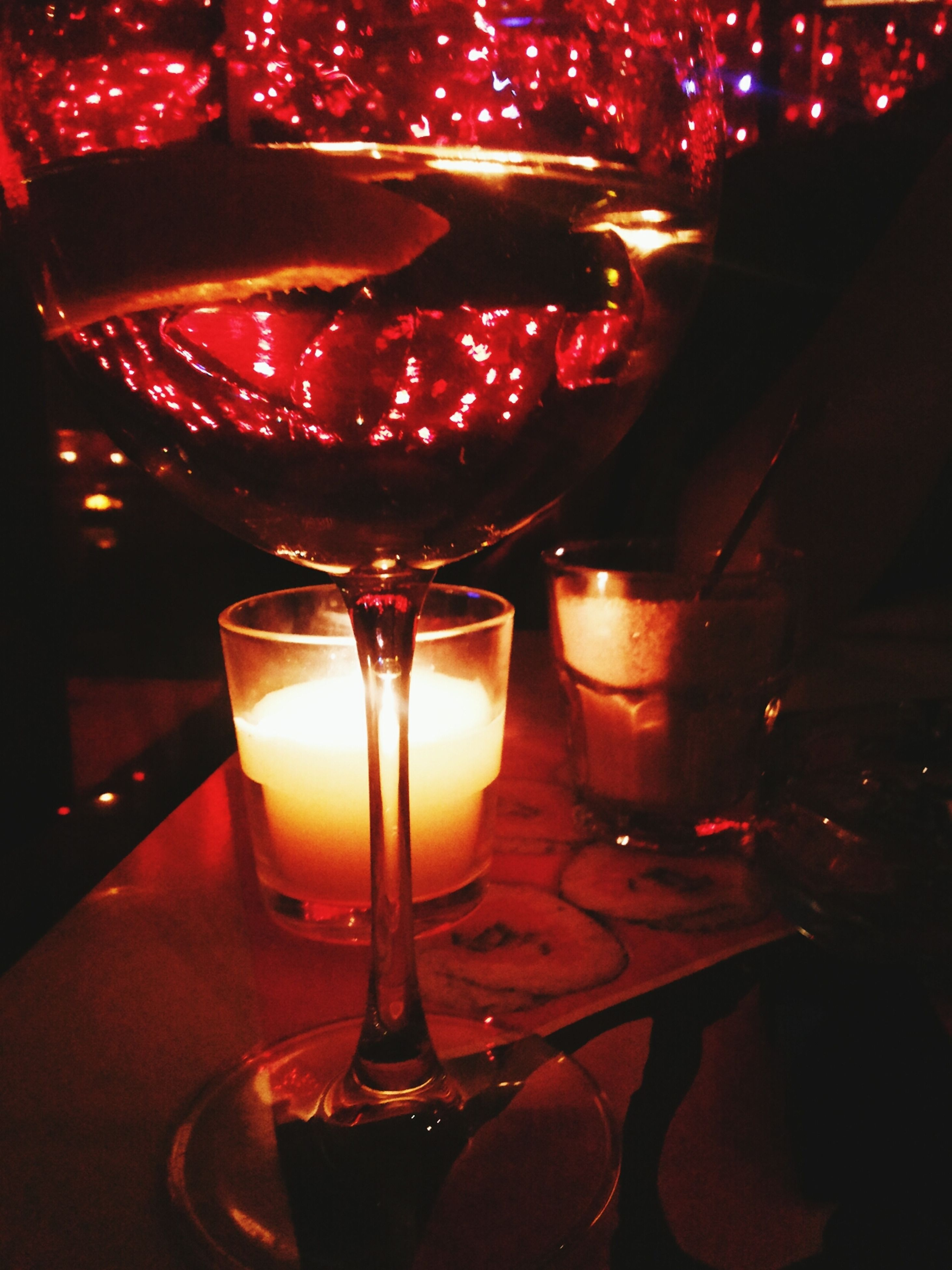 illuminated, indoors, lighting equipment, candle, night, glass - material, table, lit, glowing, transparent, drink, drinking glass, wine, close-up, light - natural phenomenon, food and drink, wineglass, restaurant, burning, alcohol