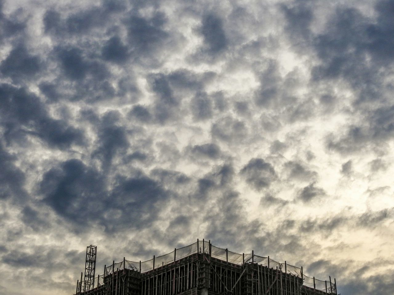 Low Angle View Of Incomplete Building Against Cloudy Sky