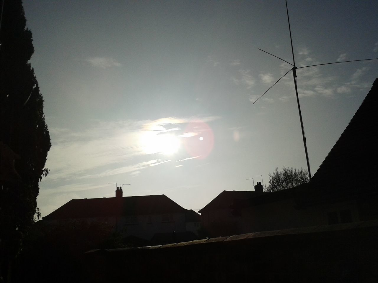Low Angle View Of Silhouette Buildings And Sun