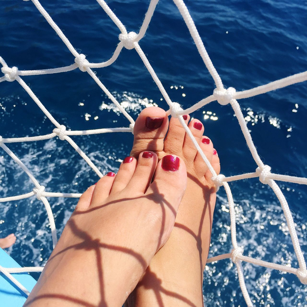 barefoot, sea, low section, water, human leg, human foot, real people, human body part, one person, day, outdoors, railing, sunlight, high angle view, women, nail polish, nautical vessel, blue, summer, boat deck, close-up, nature, beauty in nature, human hand, adult, people