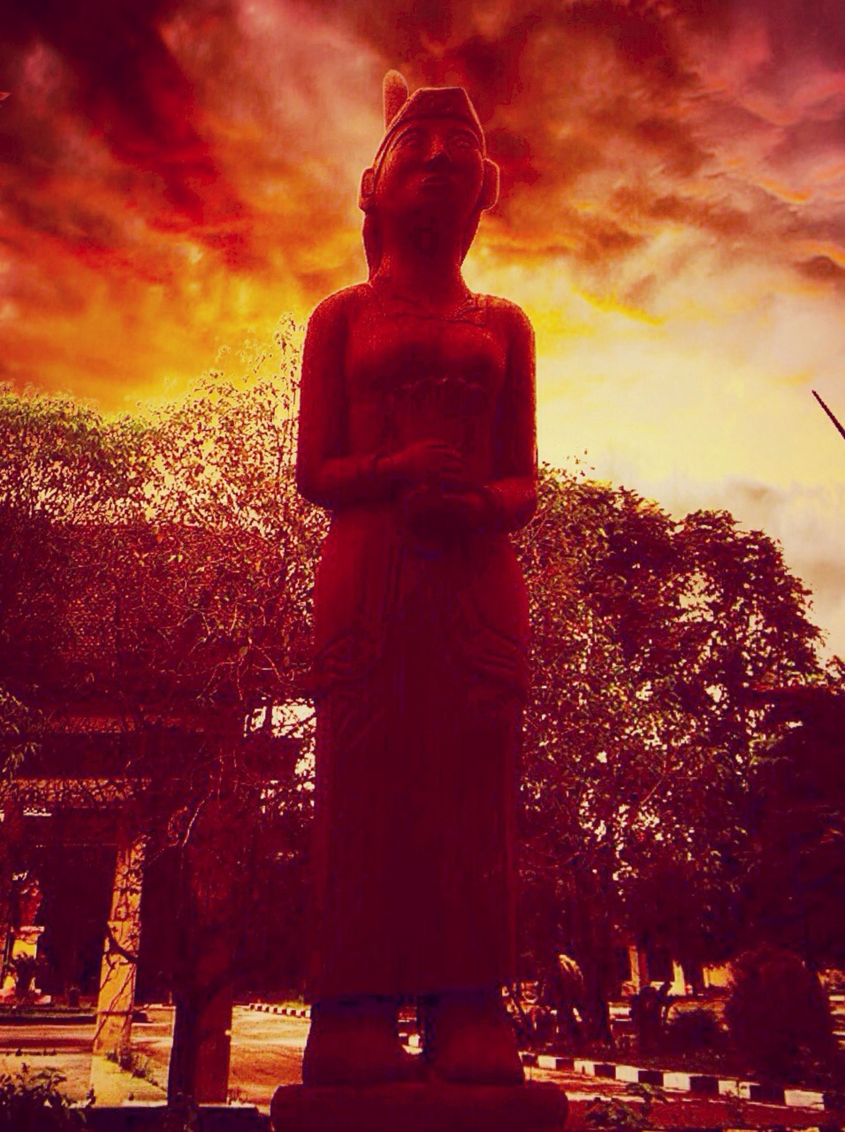 sky, statue, sunset, sculpture, cloud - sky, human representation, art and craft, religion, art, tree, spirituality, silhouette, temple - building, creativity, low angle view, orange color, place of worship, cloudy