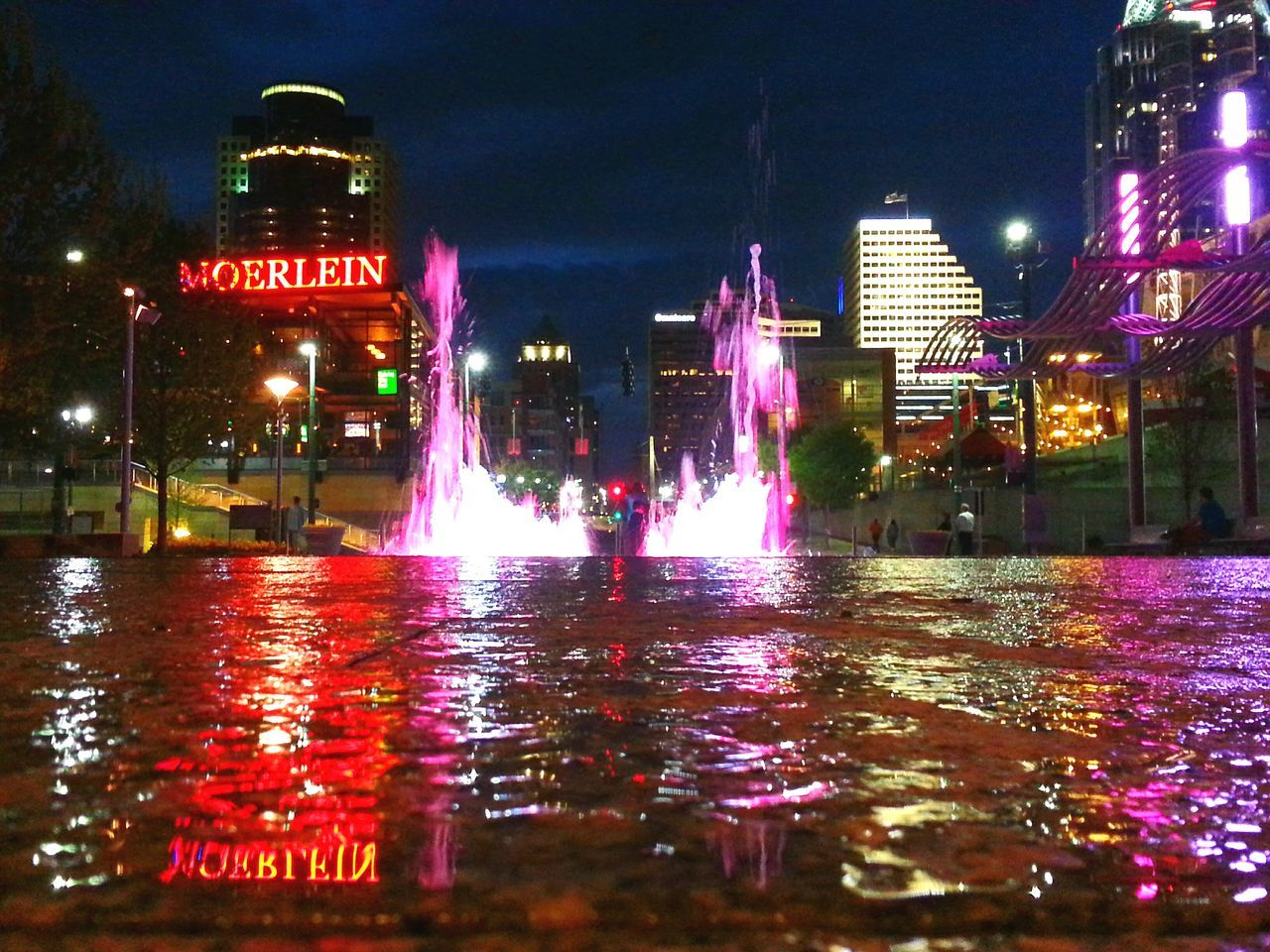 Illuminated Fountains Against Buildings In City At Night
