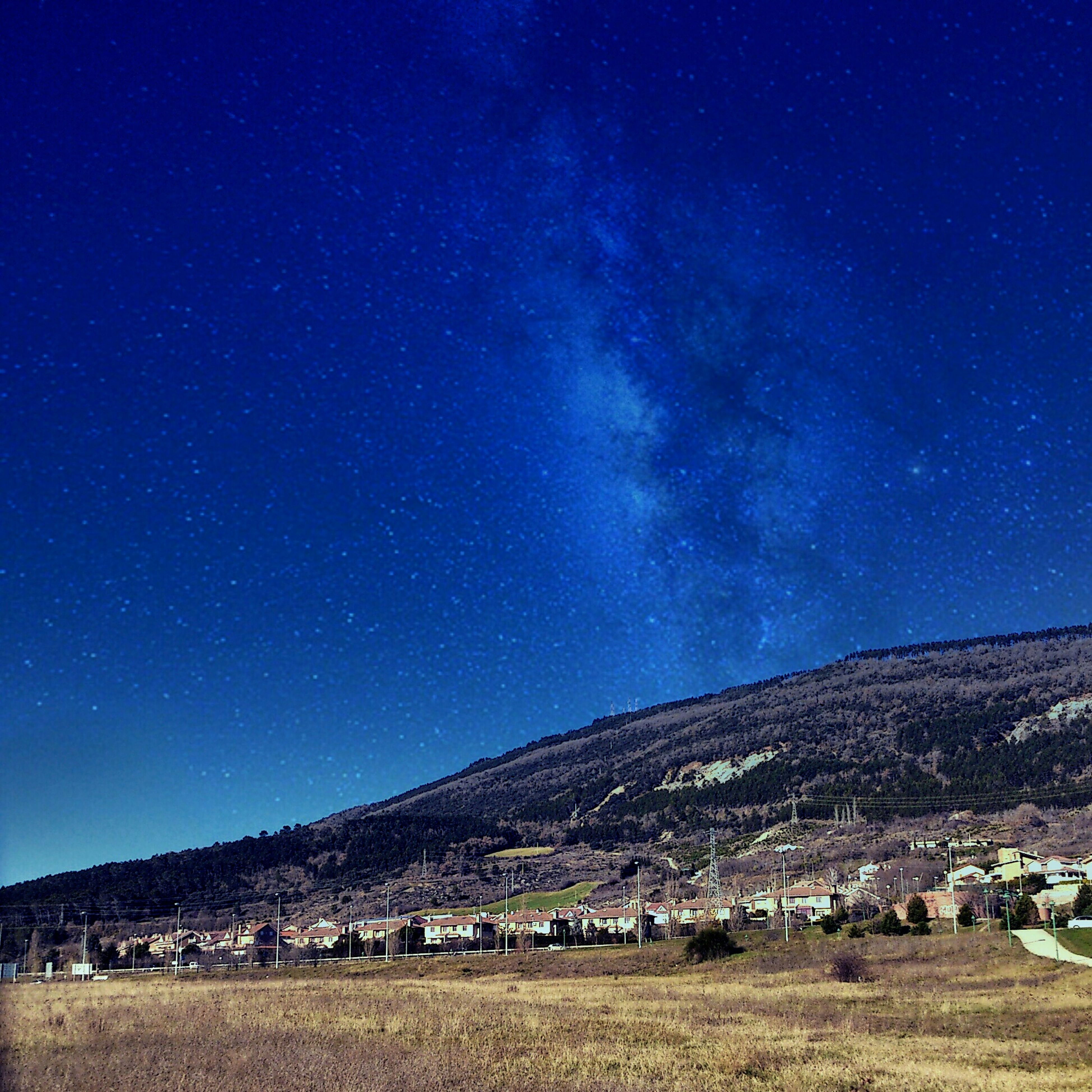 blue, night, landscape, scenics, tranquil scene, tranquility, beauty in nature, star - space, sky, mountain, nature, star field, clear sky, building exterior, field, house, idyllic, built structure, astronomy, outdoors
