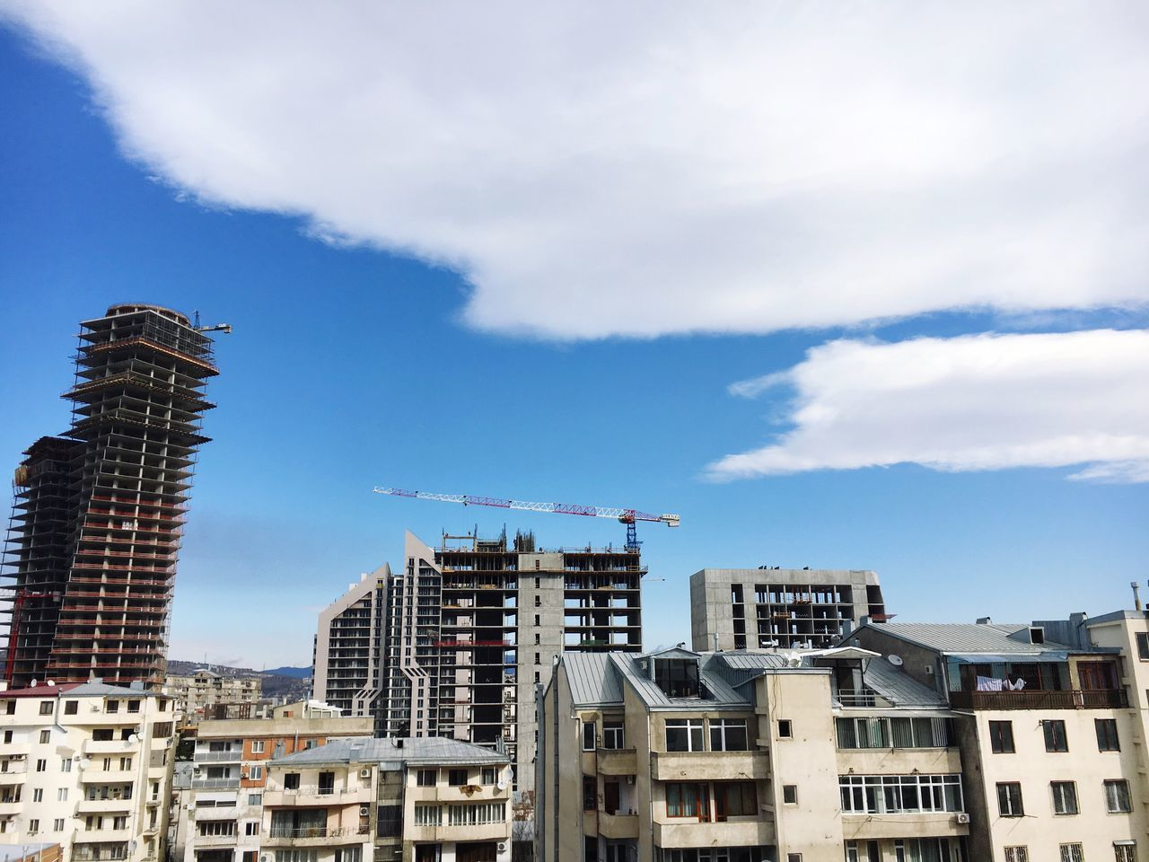 Construction in progress.. 🏢🏢🏢🏗🛠 Building Exterior Architecture Built Structure City Sky No People Cloud - Sky Outdoors Day Skyscraper Cityscape Old And New Old And New Architecture Block Of Flats Tbilisi Georgia Construction Site Construction Crane Balconies Windows Clouds And Sky Balcony View