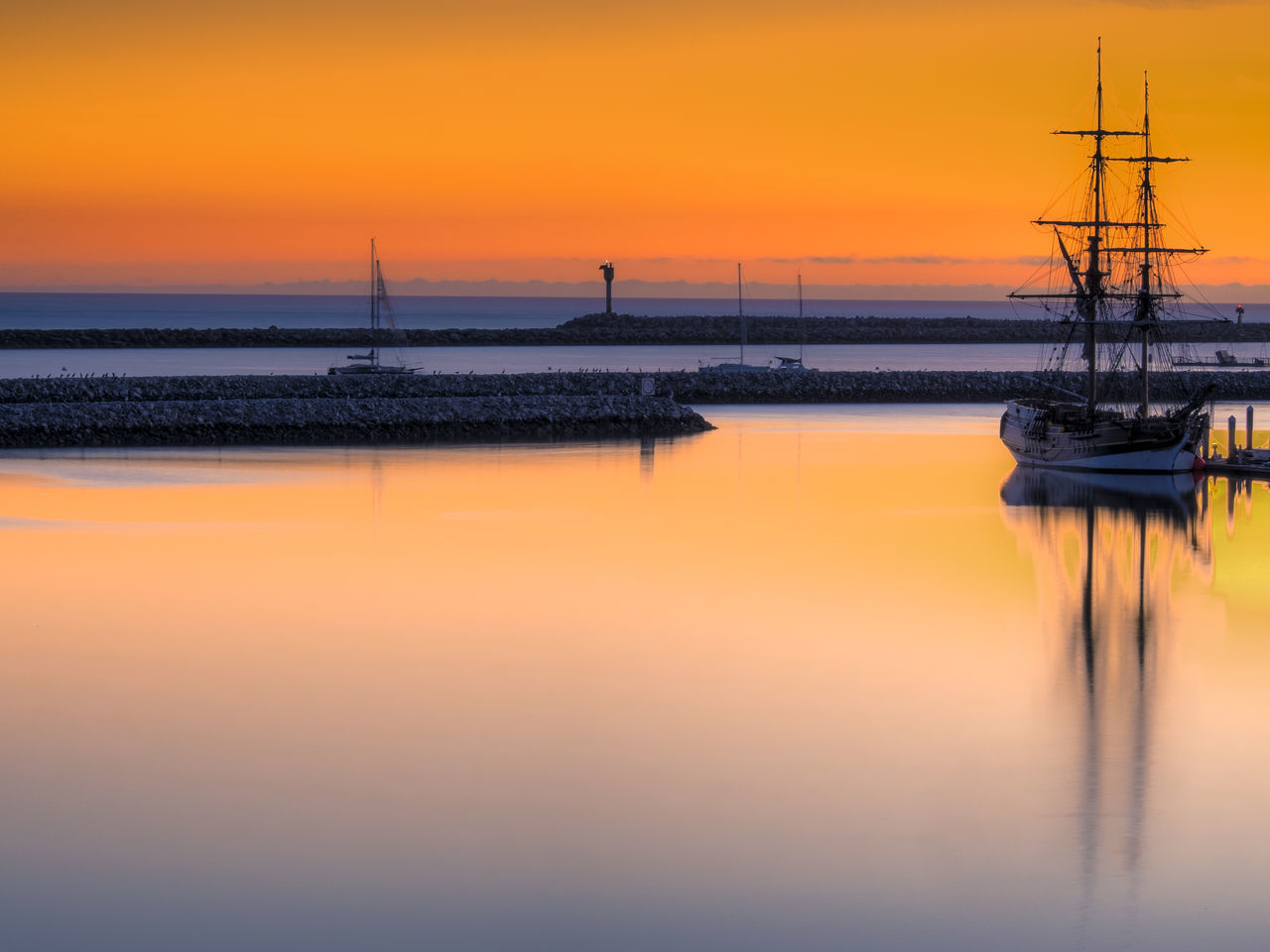 Sailboat In River Against Orange Sky During Sunset