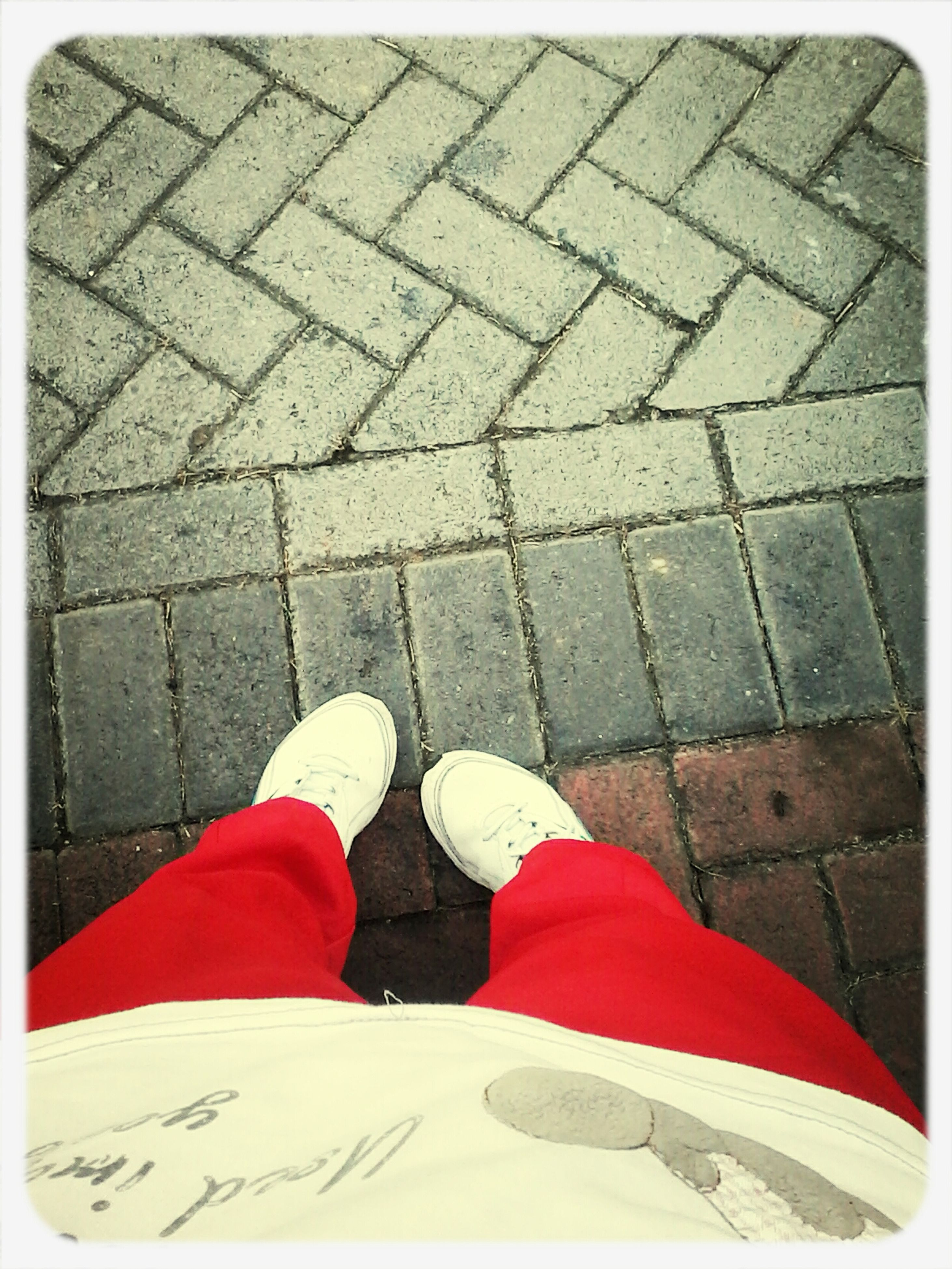 low section, transfer print, person, high angle view, shoe, auto post production filter, standing, lifestyles, street, red, footwear, leisure activity, human foot, personal perspective, cobblestone, directly above, men