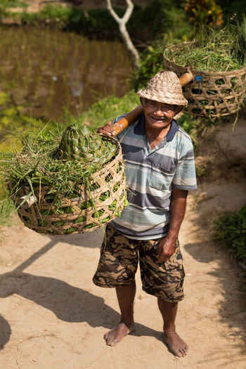 Adult Agriculture Basket Day Farm Worker Farmer Friut Basket Full Length Grass In Basket Hat Men Nature One Man Only One Person Outdoors People Sand Smiles Standing Water Working Woven Basket