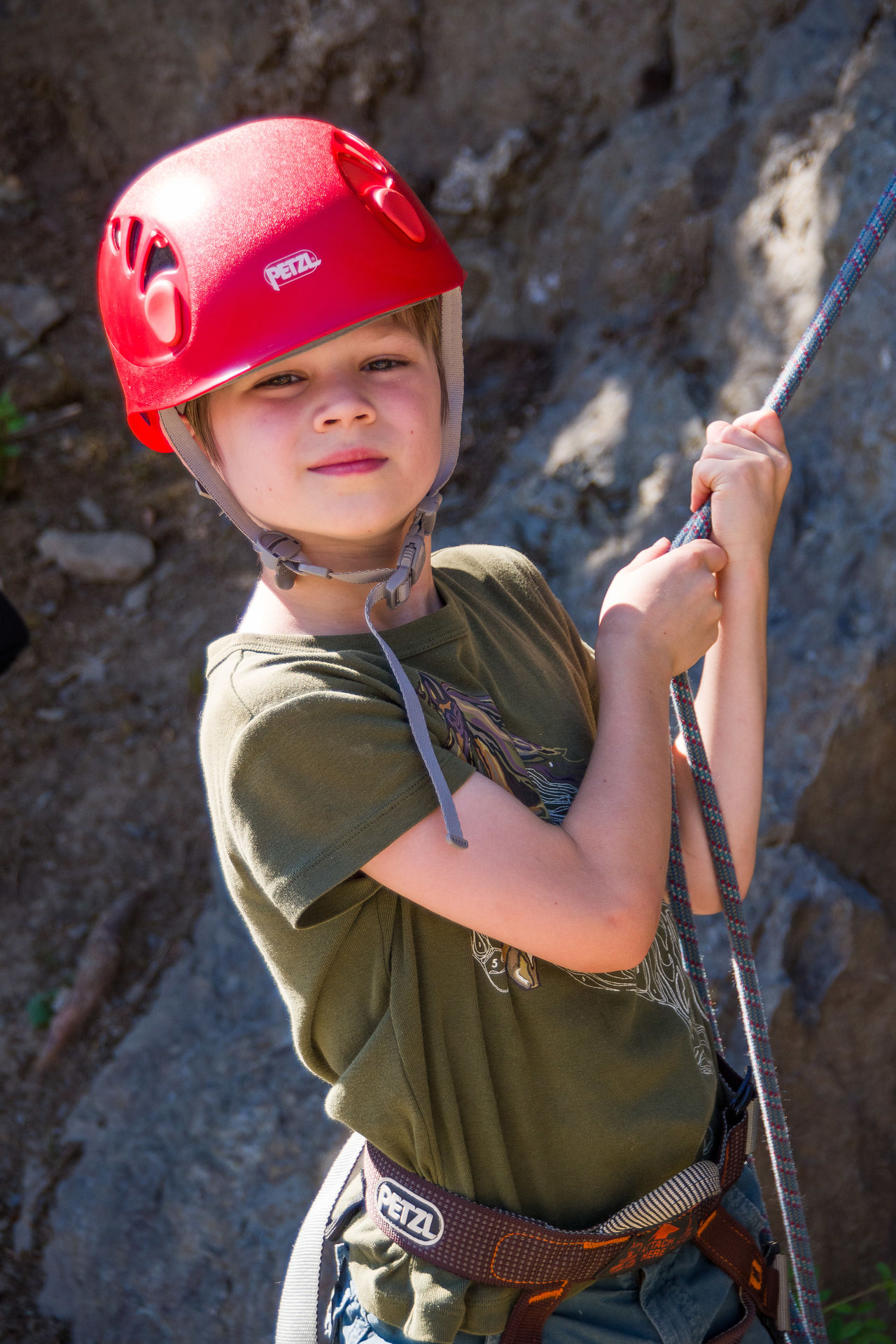 Childhood Climbing A Mountain Focus On Foreground Helmet Leisure Activity Looking At Camera Sports Young Child In Sunlight And Shadow