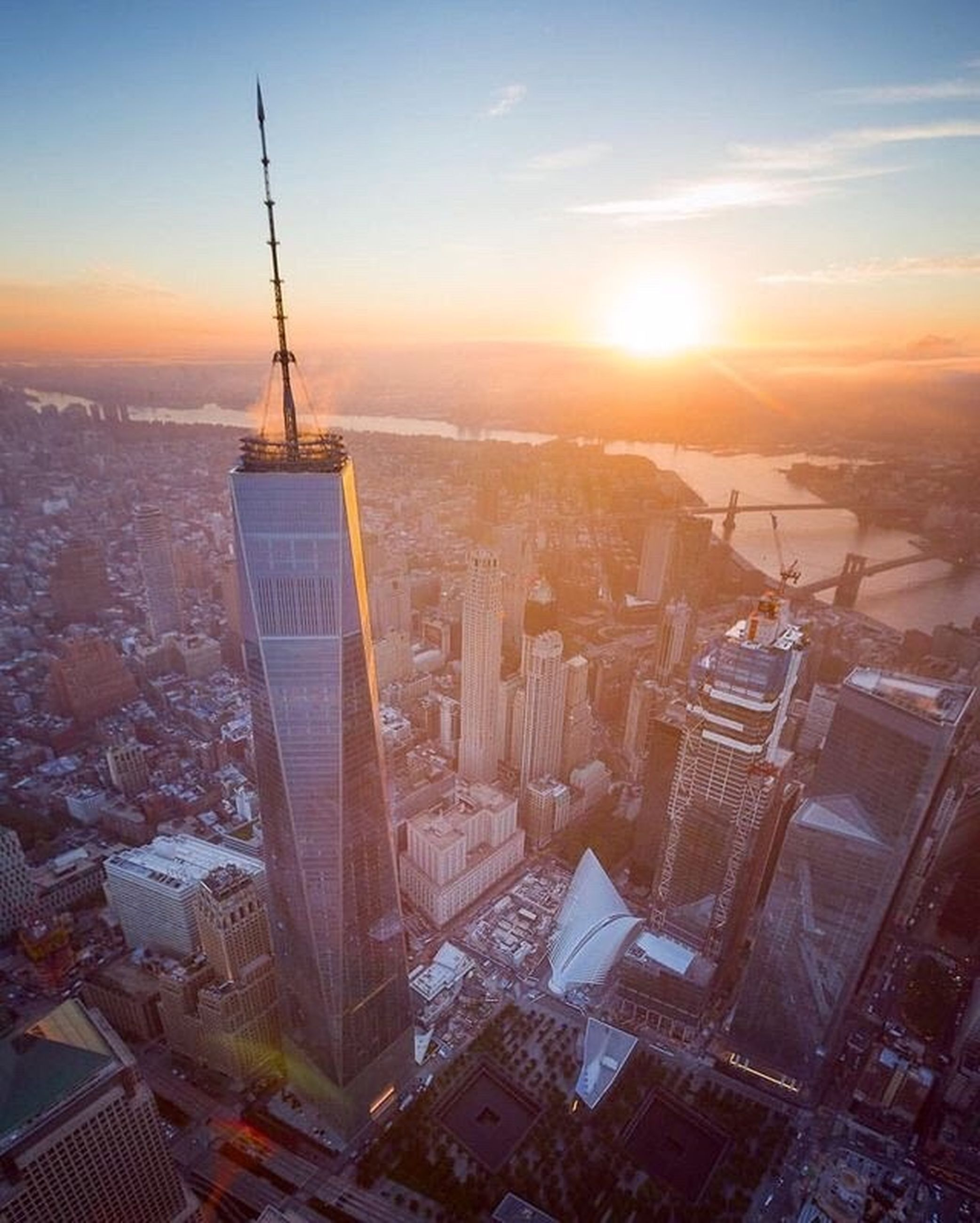 cityscape, skyscraper, city, architecture, building exterior, tower, sunset, development, urban skyline, aerial view, travel destinations, no people, sun, city life, built structure, corporate business, outdoors, modern, sky, day