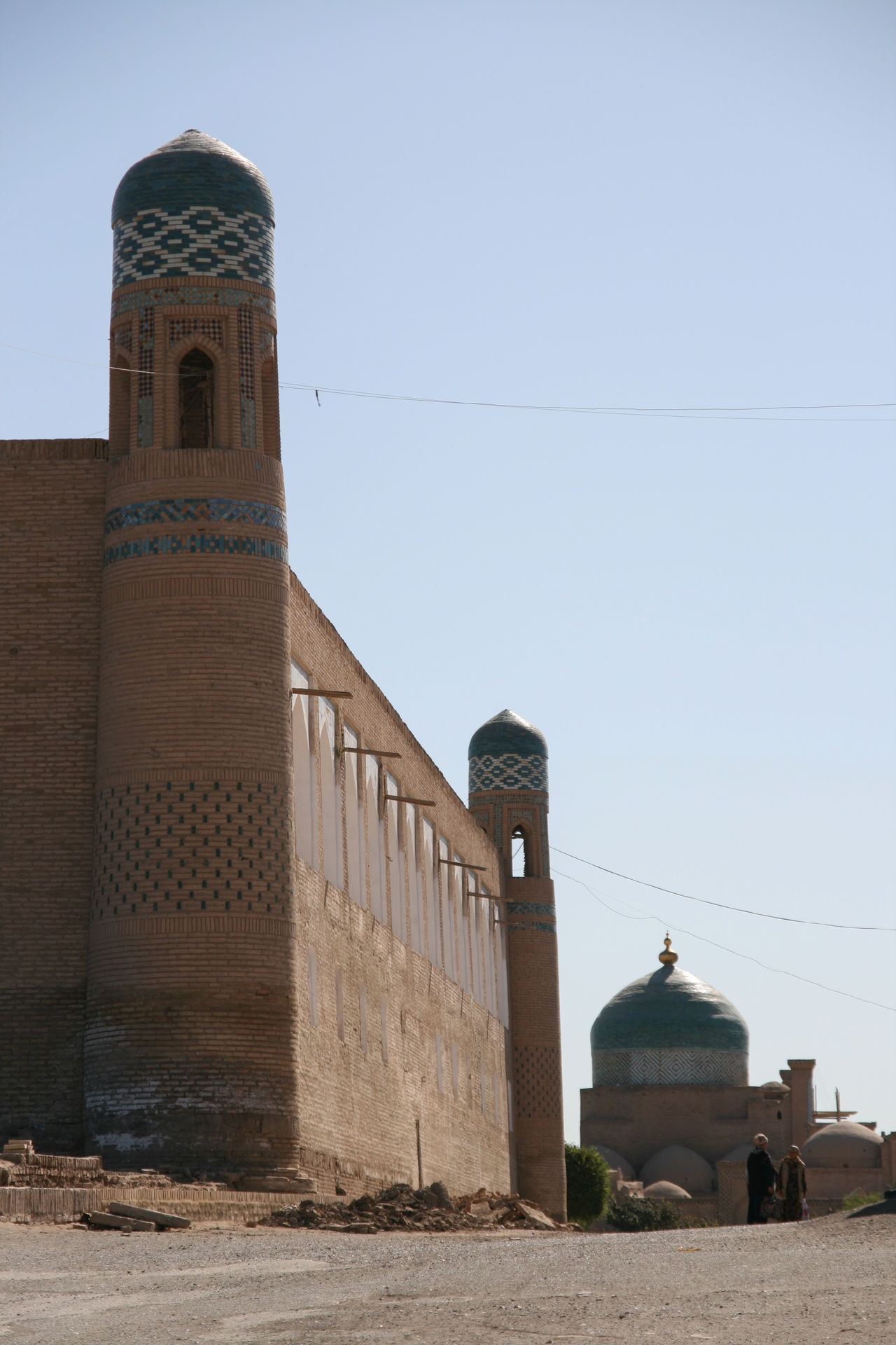 Architecture Architecture Blue Building Exterior Clear Sky Culture Dome Famous Place Historic History International Landmark Islam Islamic Architecture Khiva Mosque Place Of Worship Religion Silk Road Spirituality Tower Two People Uzbekistan Women