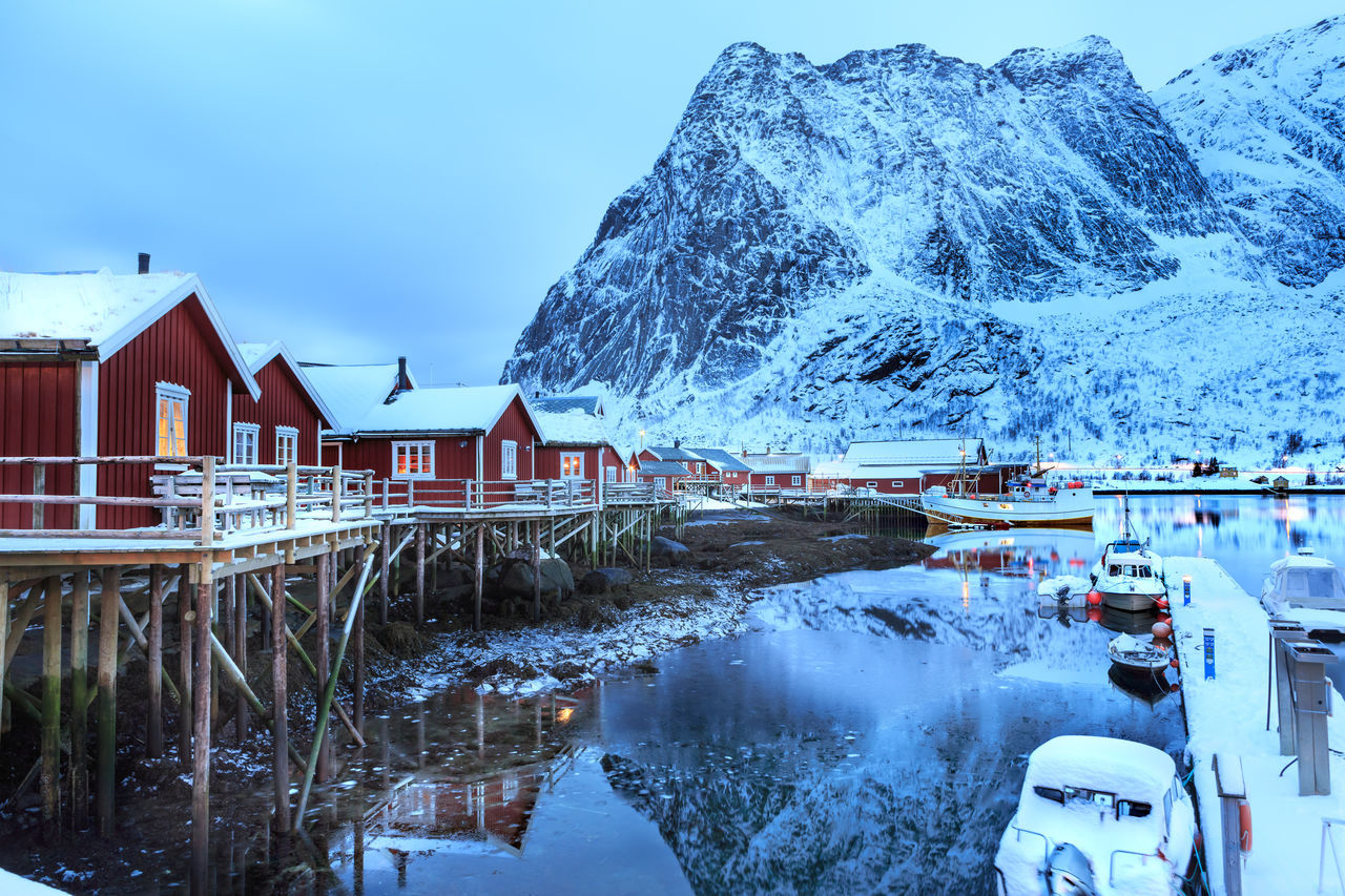 The fisherman village Reine on Lofoten Islands by night, Norway Architecture Barents Sea, Lofoten Islands, Northern, Reine, Town, Arctic, Atlantic, Coast, Cold, Europe, Fishing, Fjord, Harbor, Holiday, Ice, Landscape, Mountains, Nature, Night, Nordic, Nordland, North, North Sea, Norway, Norwegian, Ocean, Outdoor, Outdoors, Polar C Beauty In Nature Building Exterior Built Structure Cold Temperature Day House Mountain Nature No People Outdoors Reflection Scenics Sky Snow Tranquil Scene Tranquility Water Winter