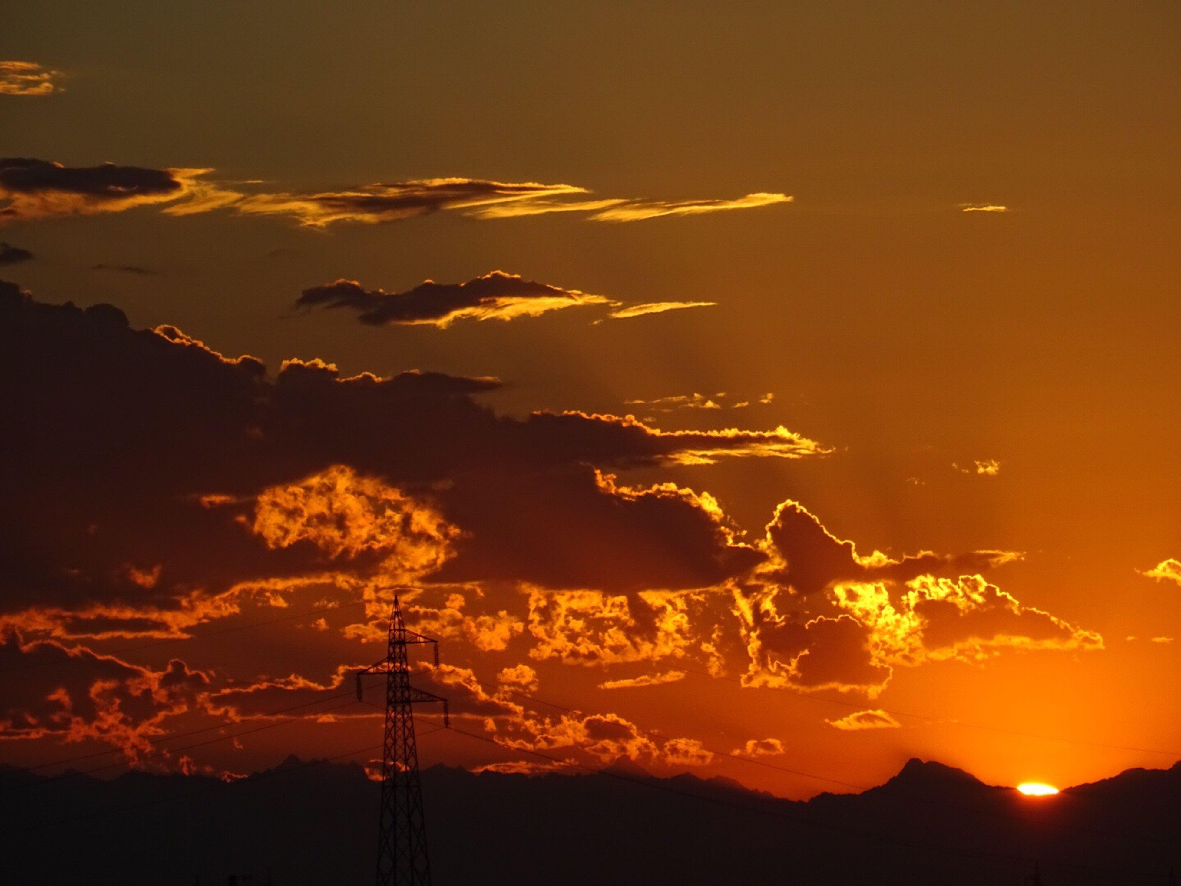 sunset, silhouette, orange color, scenics, sky, beauty in nature, tranquil scene, sun, tranquility, idyllic, nature, cloud - sky, dramatic sky, dark, majestic, cloud, outdoors, back lit, outline, landscape, moody sky, no people, power supply, non-urban scene, sunbeam