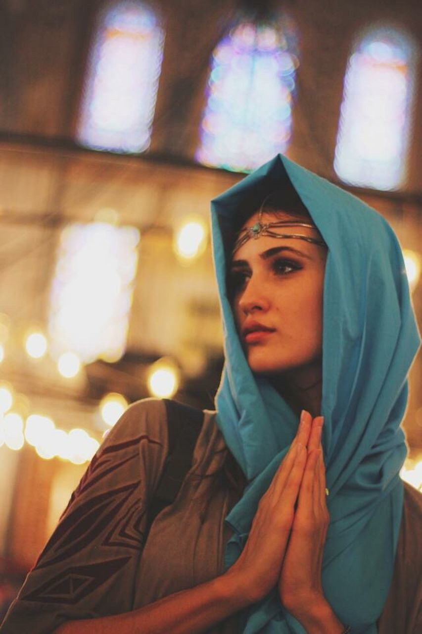 religion, one person, indoors, front view, spirituality, focus on foreground, real people, lifestyles, young women, young adult, close-up, night, portrait, illuminated, beautiful woman, people