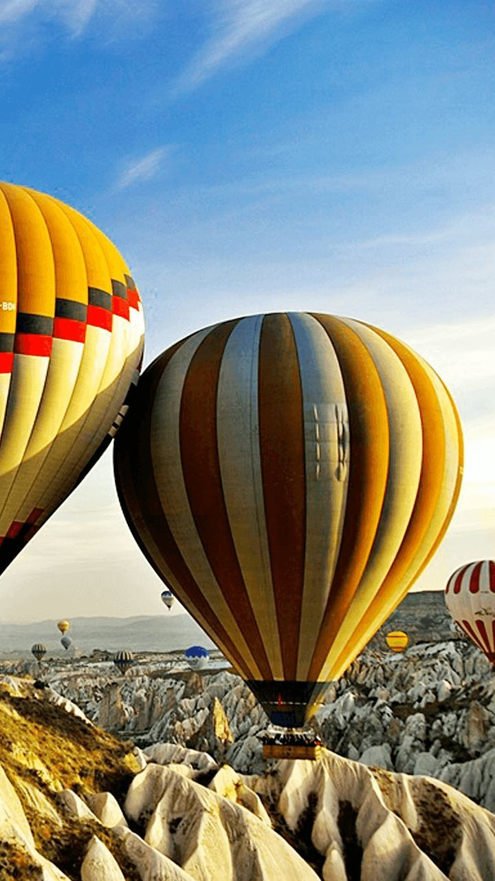 hot air balloon, air vehicle, sky, transportation, ballooning festival, outdoors, adventure, mid-air, flying, day, landscape, multi colored, mountain, no people, nature