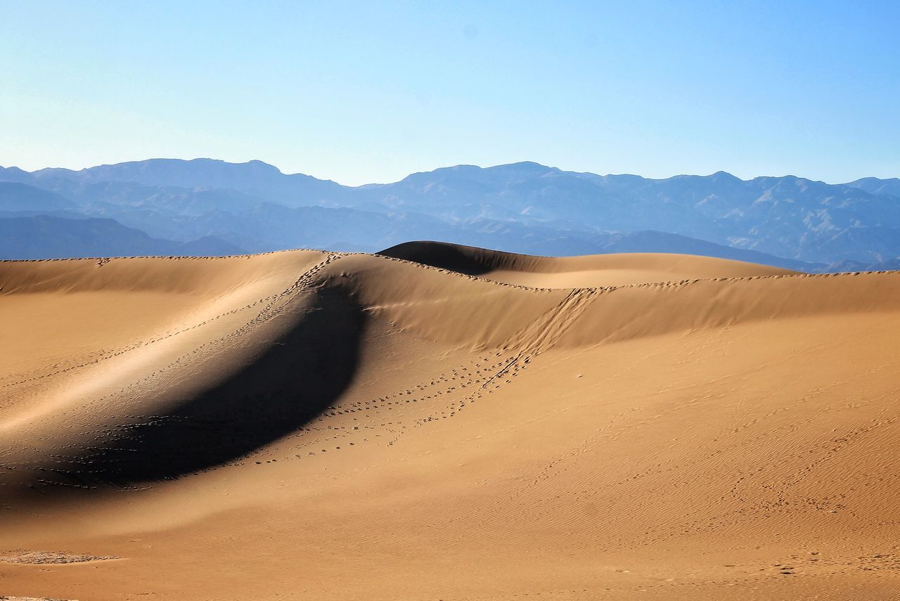 Scenic View Of Desert And Mountains Against Clear Sky