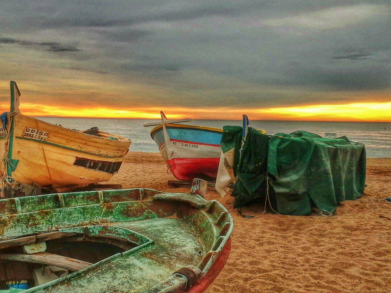 Boats Moored On Sandy Beach At Sunset