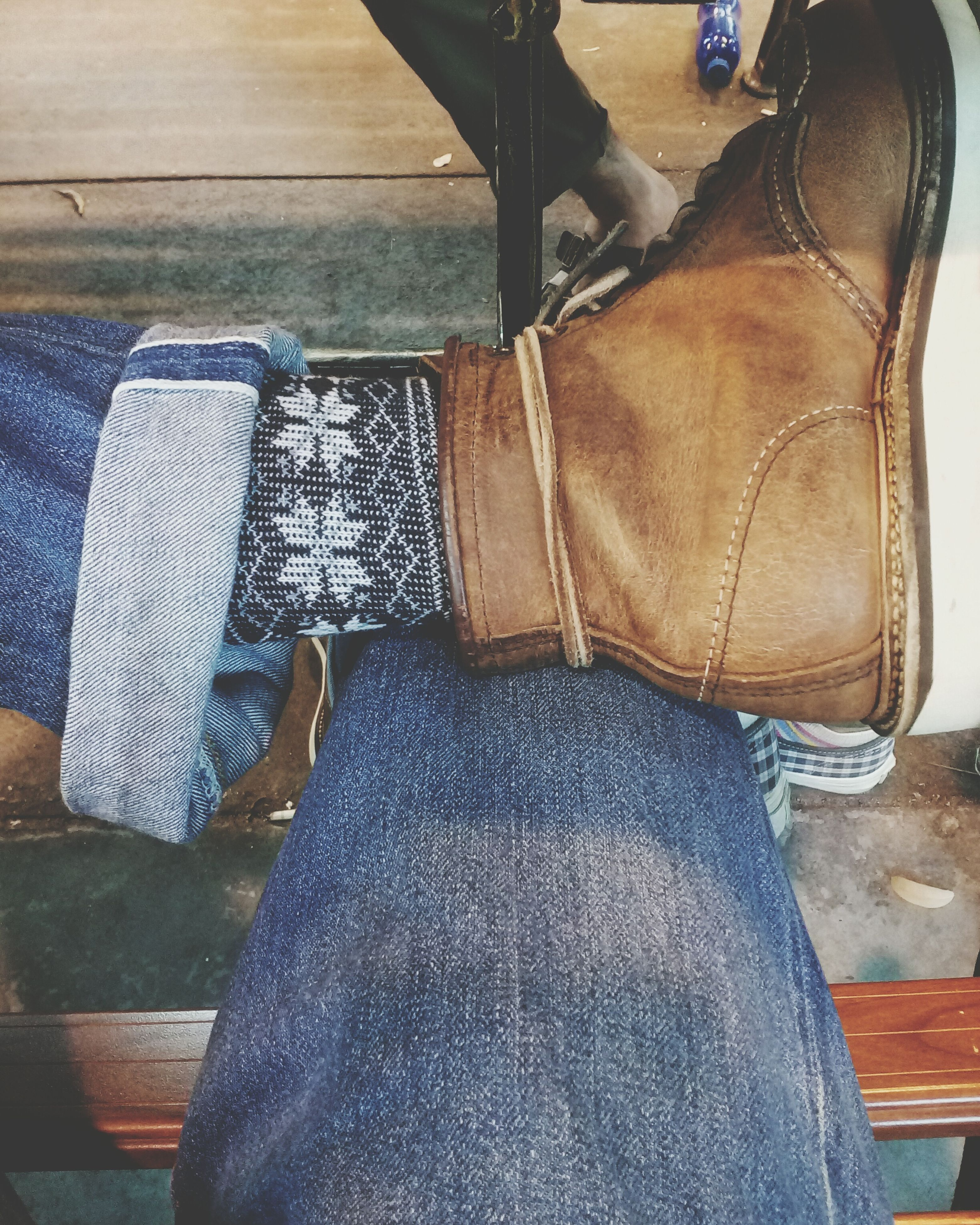 low section, person, shoe, jeans, footwear, indoors, human foot, personal perspective, chair, part of, fashion, sitting, wood - material, high angle view, relaxation, standing, pair