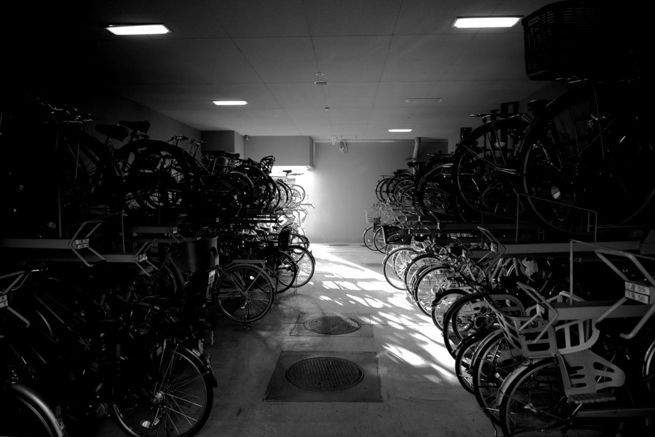 in a row, indoors, bicycle, abundance, illuminated, large group of objects, no people, bicycle rack, day