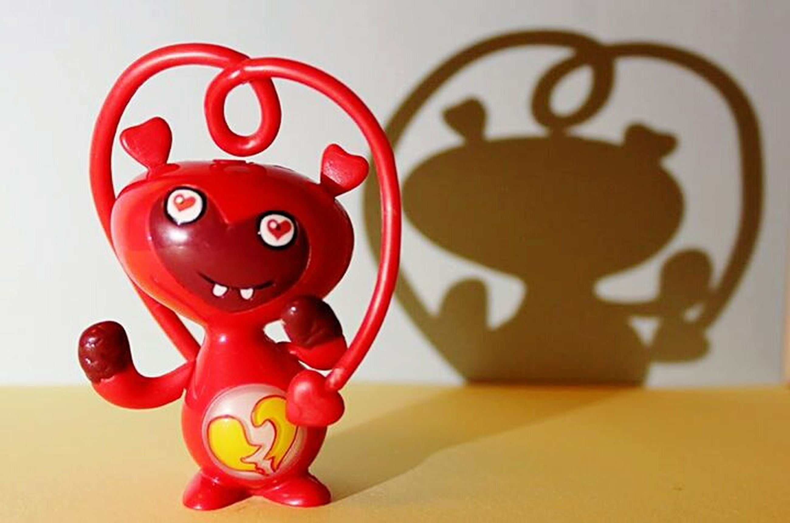 red, indoors, table, close-up, still life, toy, animal representation, creativity, art, childhood, art and craft, wall - building feature, no people, text, human representation, focus on foreground, communication, single object, circle, anthropomorphic face