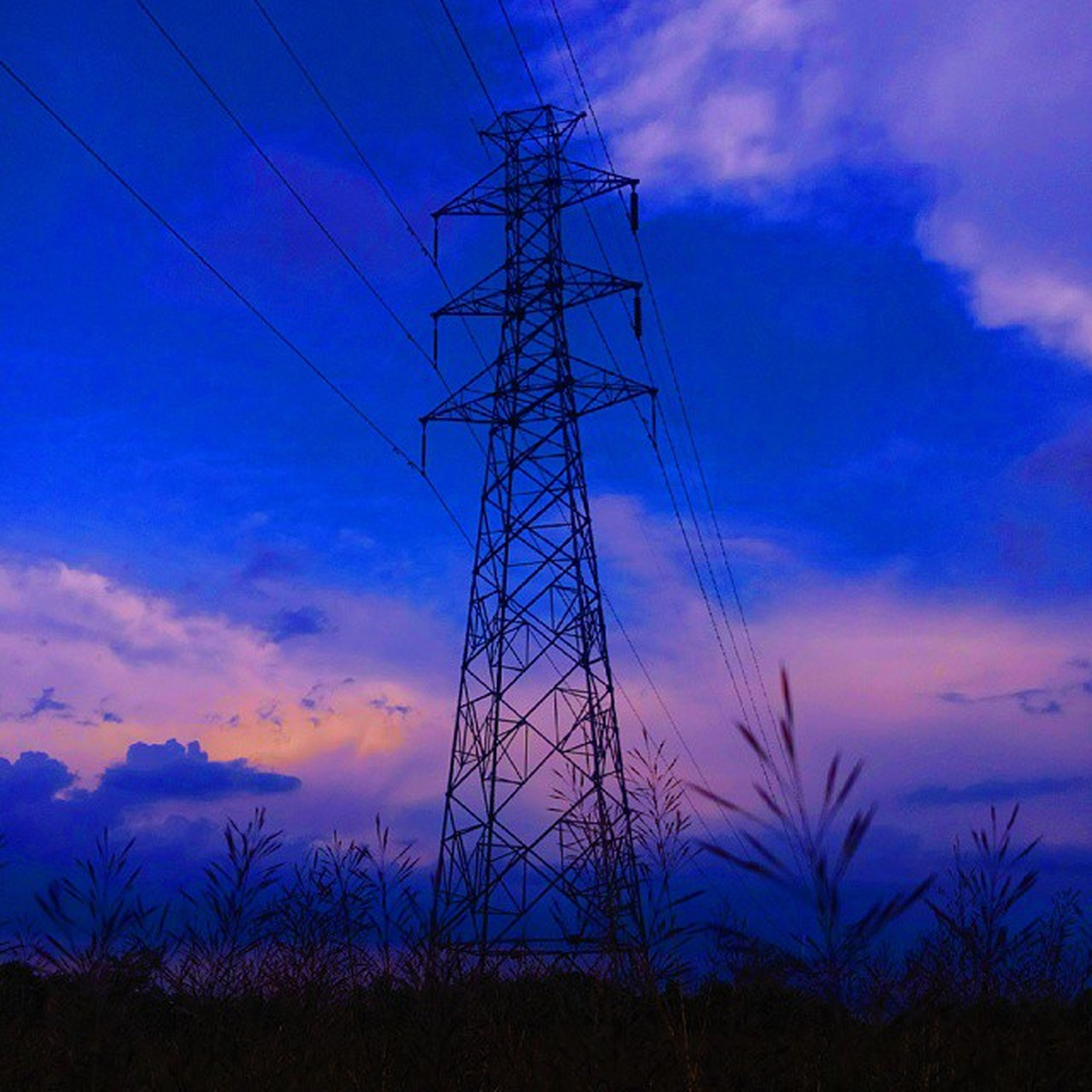 power line, electricity pylon, power supply, electricity, low angle view, fuel and power generation, connection, sky, cable, silhouette, technology, blue, sunset, cloud - sky, cloud, power cable, dusk, electricity tower, nature, outdoors