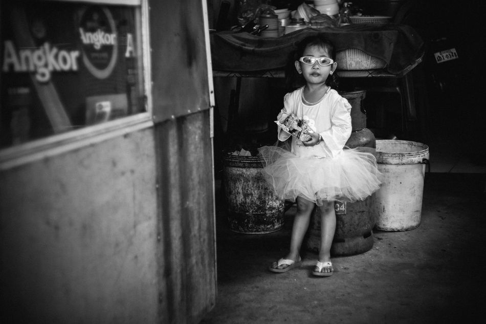 Hello from Angkor ;) That little girl is daughter of a family in Angkor! We first met her at a small local restaurant when her parent were busy to cook our meals. She knew how to play by herself, like wearing on her pinky eyes glasses, running around us and she definitely looked like a little fashionista. Maybe she has a big dream inside ;) Bnw_captures Bnw_collection Bnw_friday_eyeemchallenge Bnw_life Hoang Ann Week On Eyeem