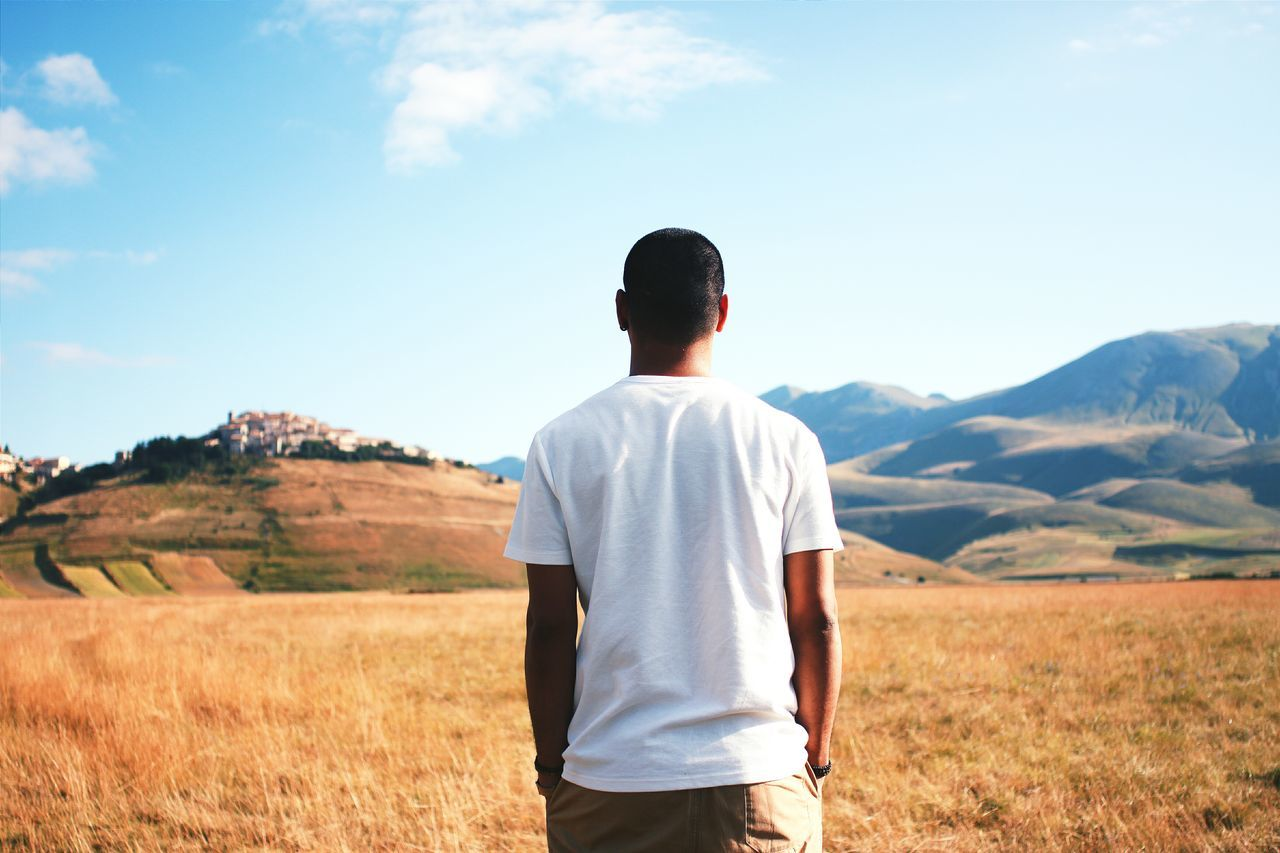 REAR VIEW OF Black MAN STANDING ON FIELD In Italy