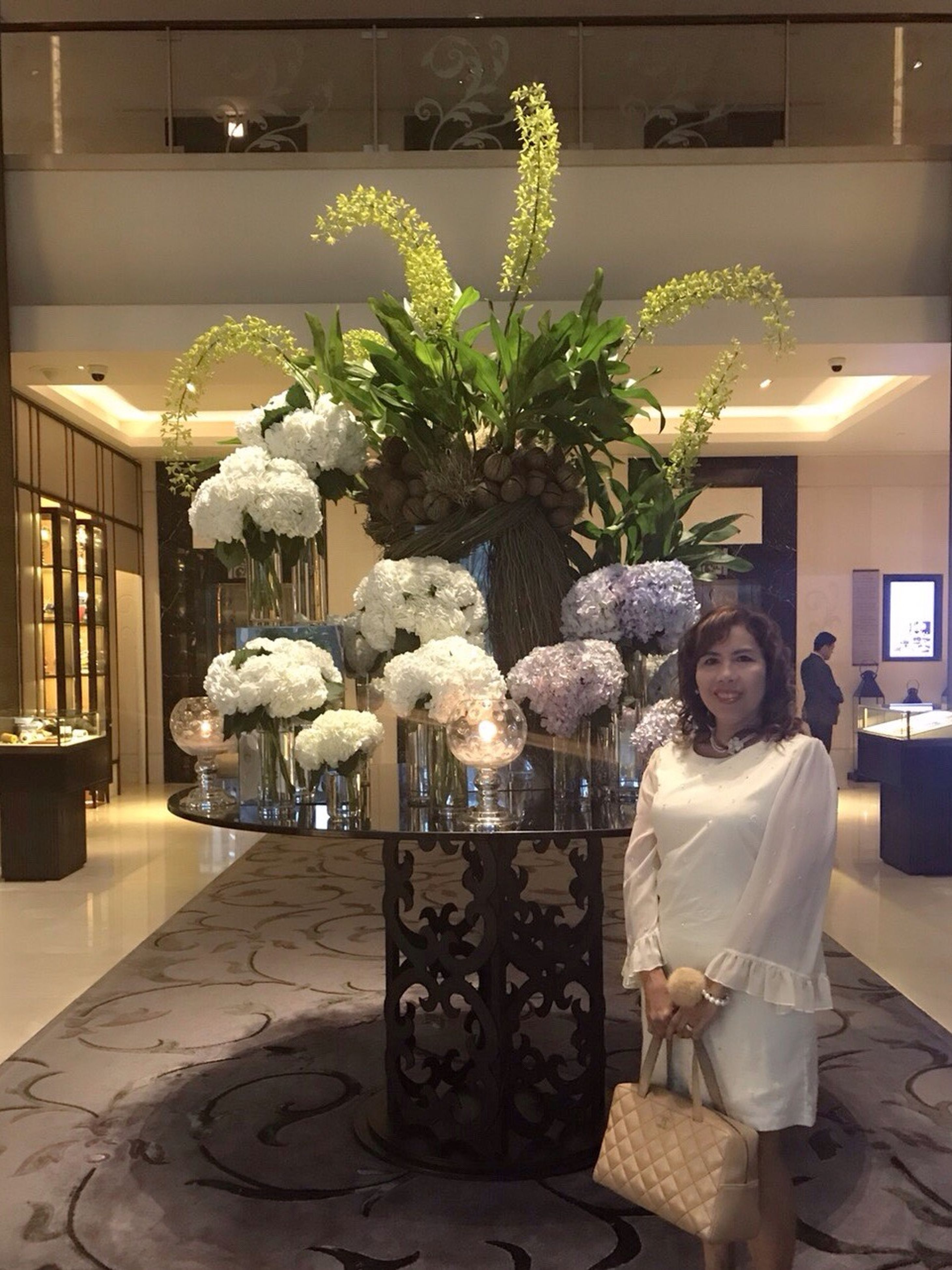 indoors, real people, flower, one person, home interior, looking at camera, luxury, standing, women, lifestyles, home showcase interior, young women, portrait, bouquet, young adult, night, illuminated, architecture, tree, people
