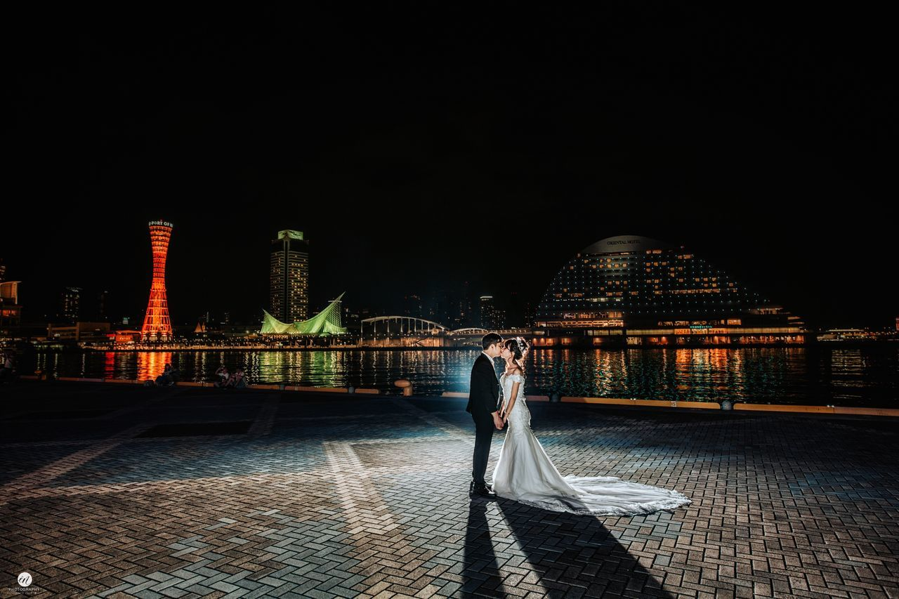 night, real people, built structure, building exterior, architecture, illuminated, rear view, two people, outdoors, women, lifestyles, men, standing, full length, togetherness, clear sky, city, sky, adult, people